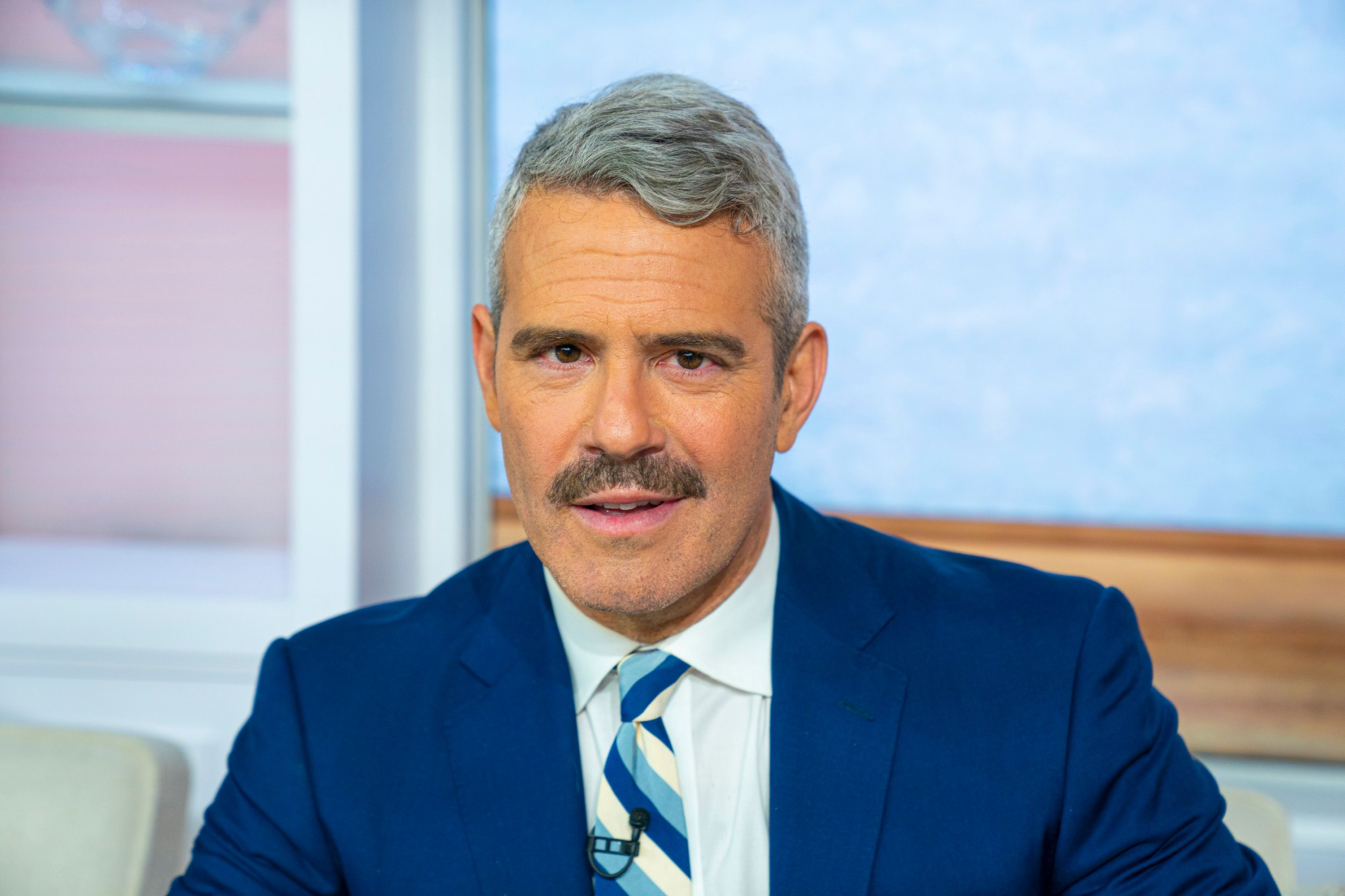 Andy Cohen headshot, wearing blue suit and has a mustache.