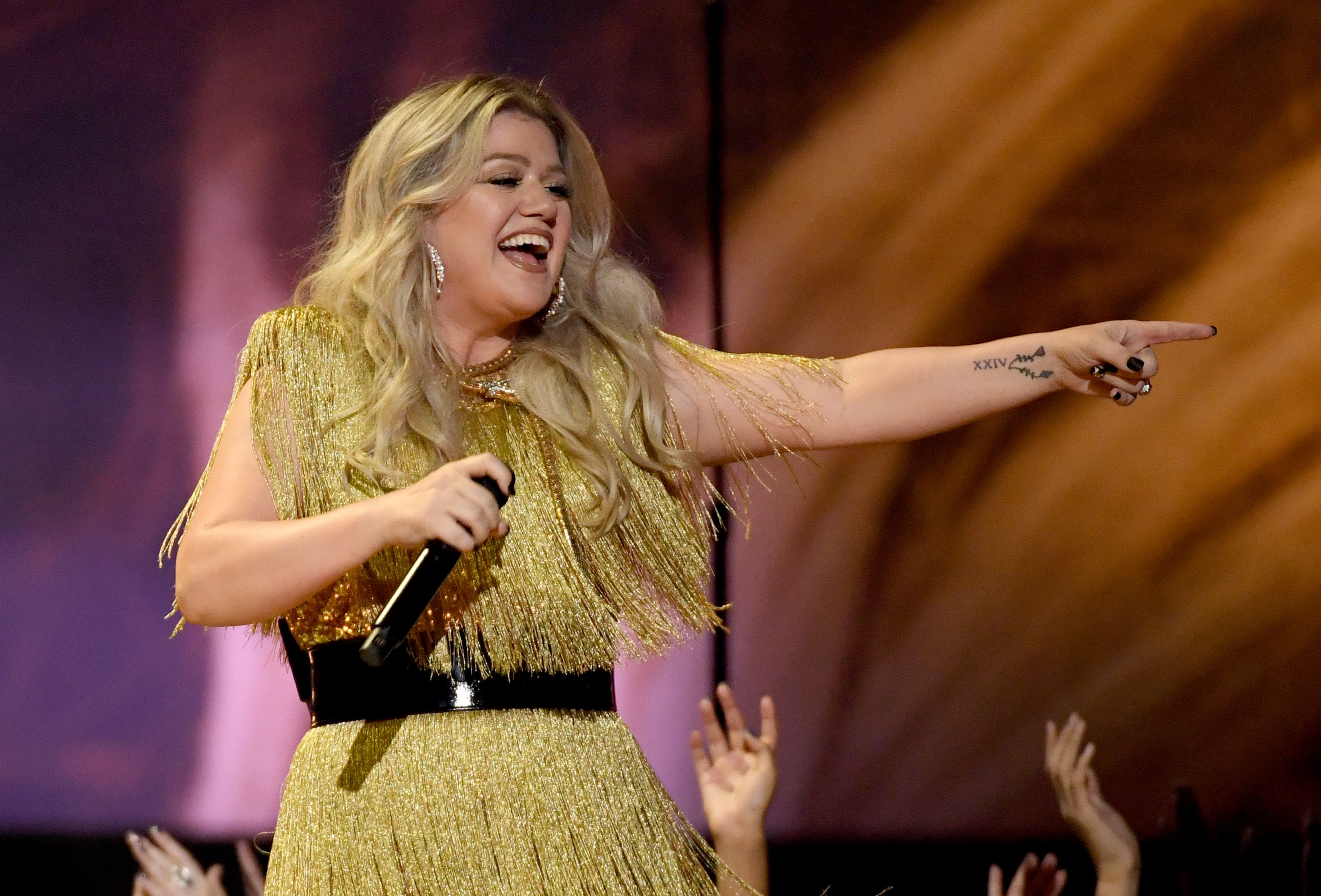 Kelly Clarkson pointing in gold fringe dress