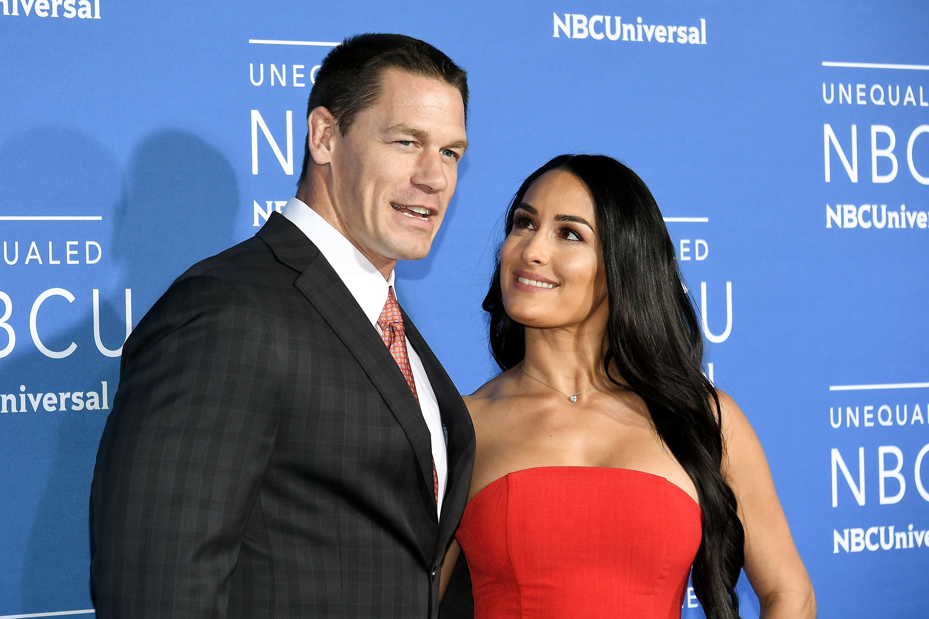 Nikki Bella wears a red dress and stares at boyfriend John Cena at an event.