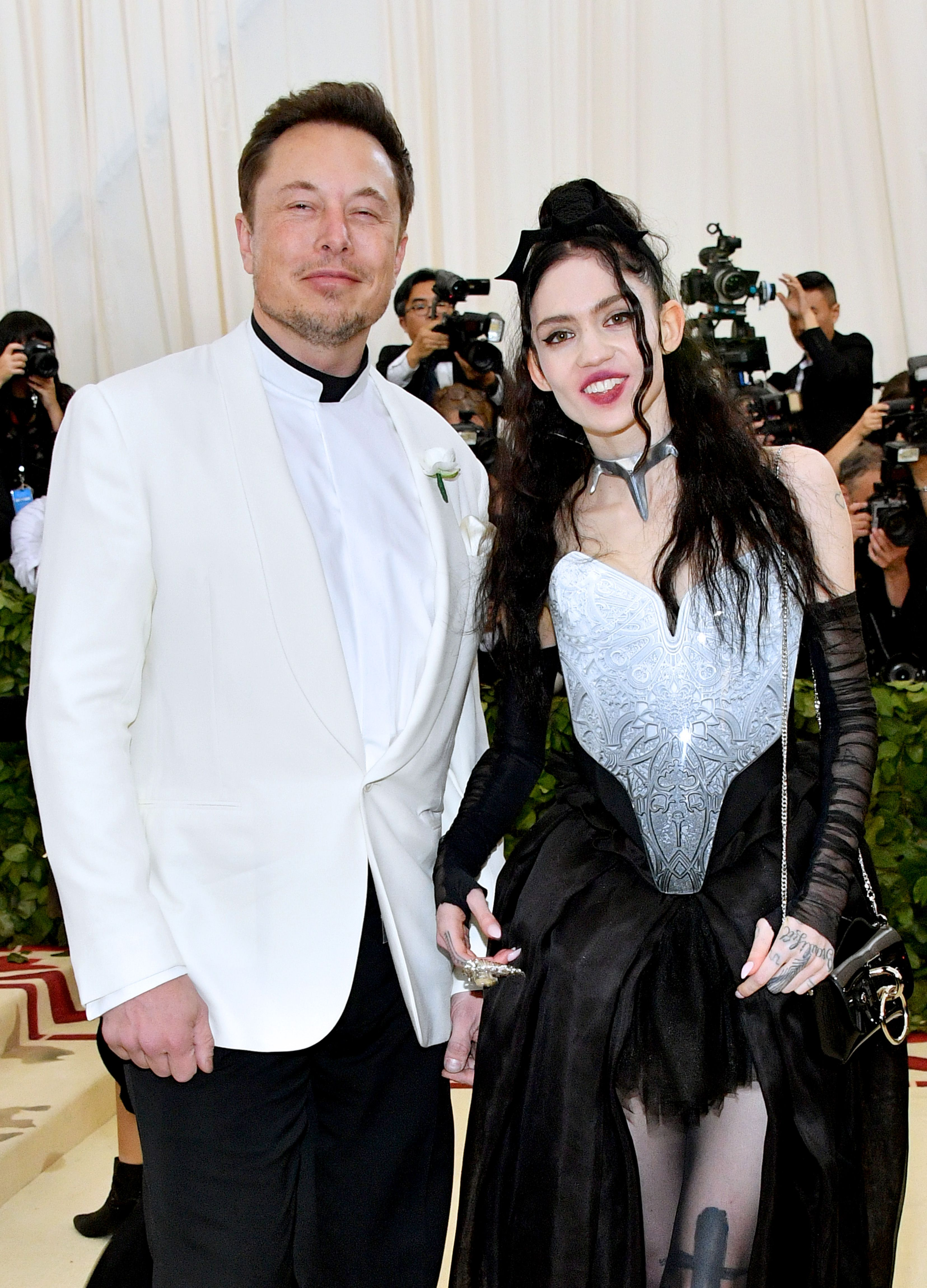 Elon Musk and Grimes pose for a photo.