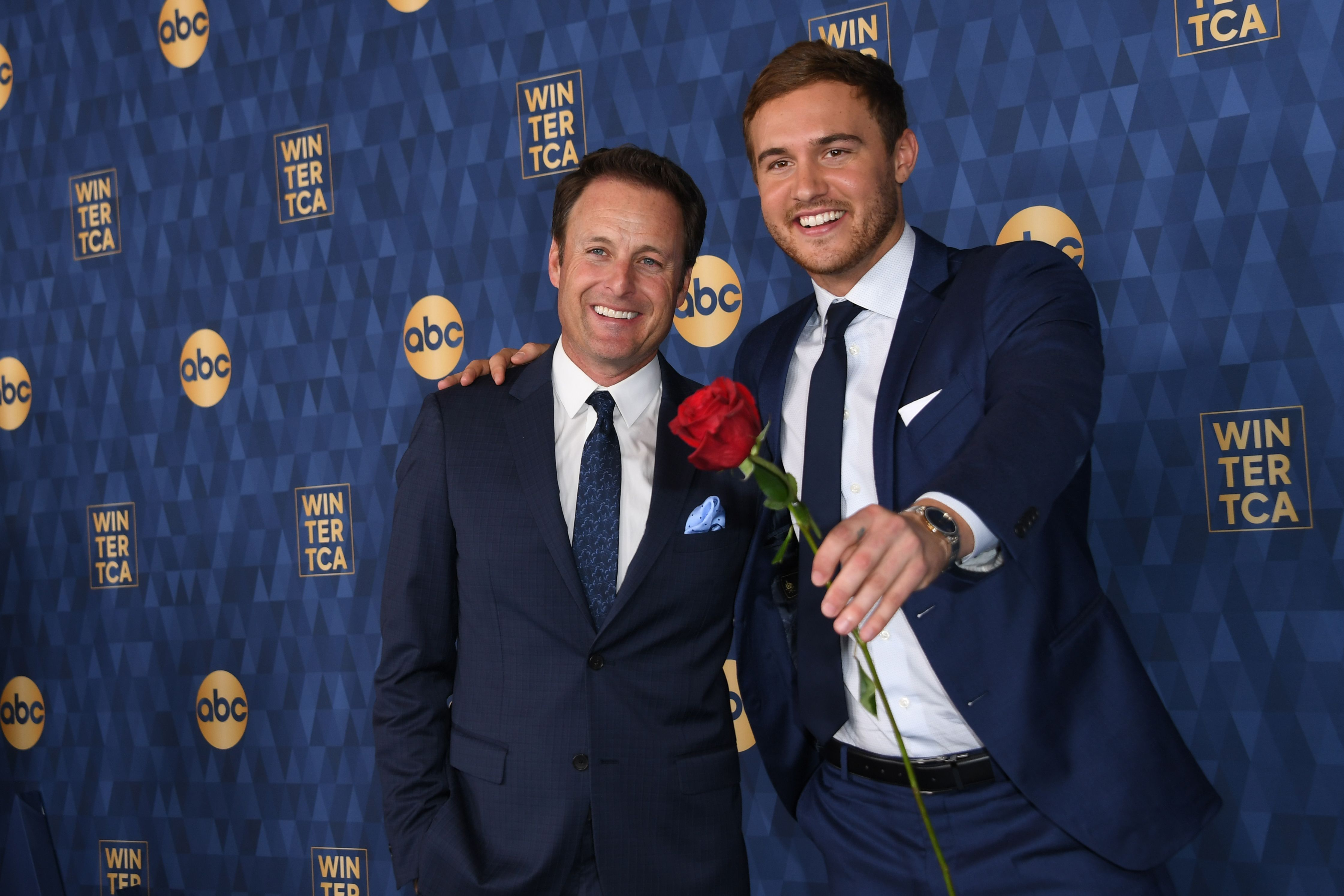 Chris Harrison (left) poses with Peter Weber (right) who holds out a rose