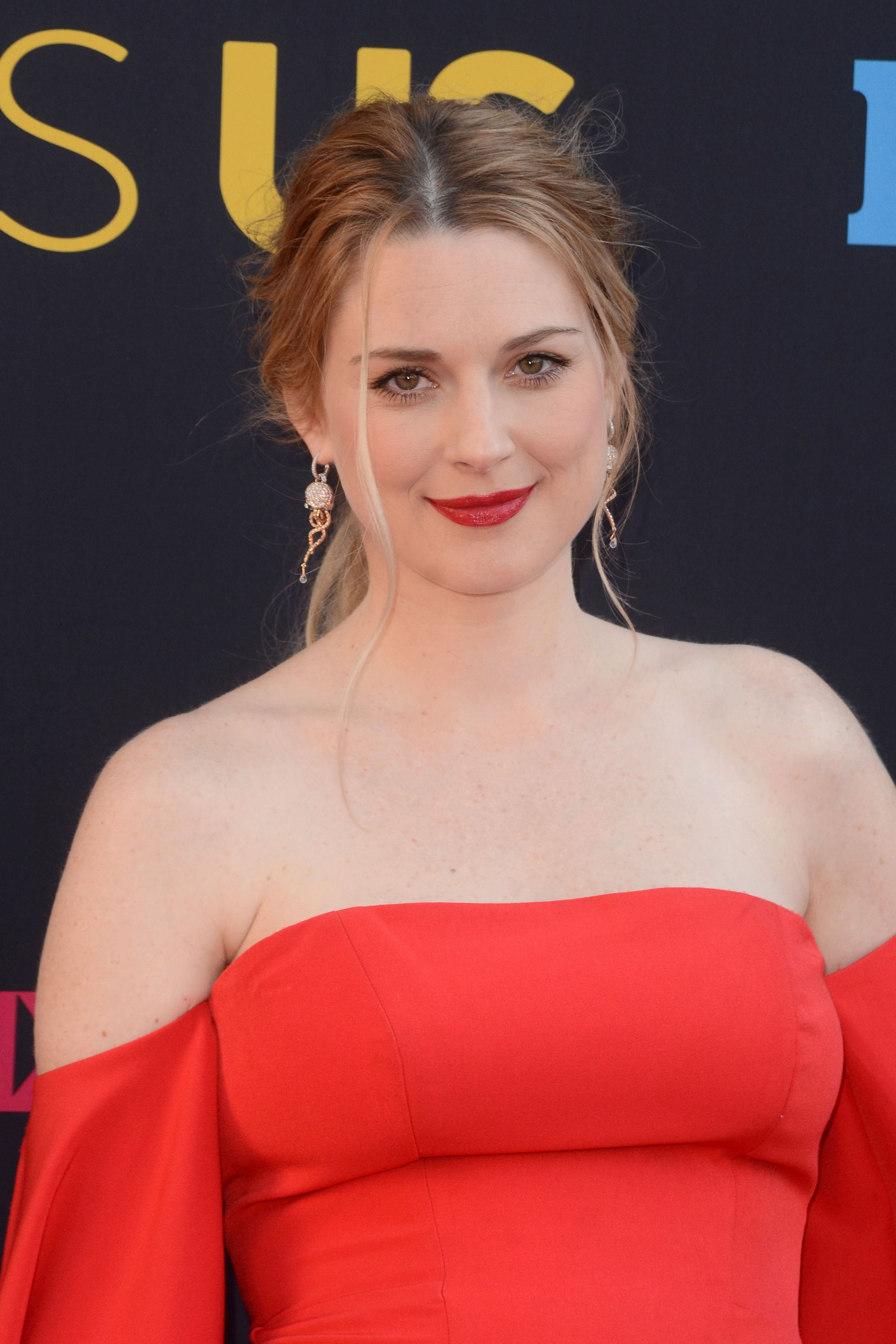 Alexandra Brackenridge wears an off-the-shoulder red dress with her hair up.