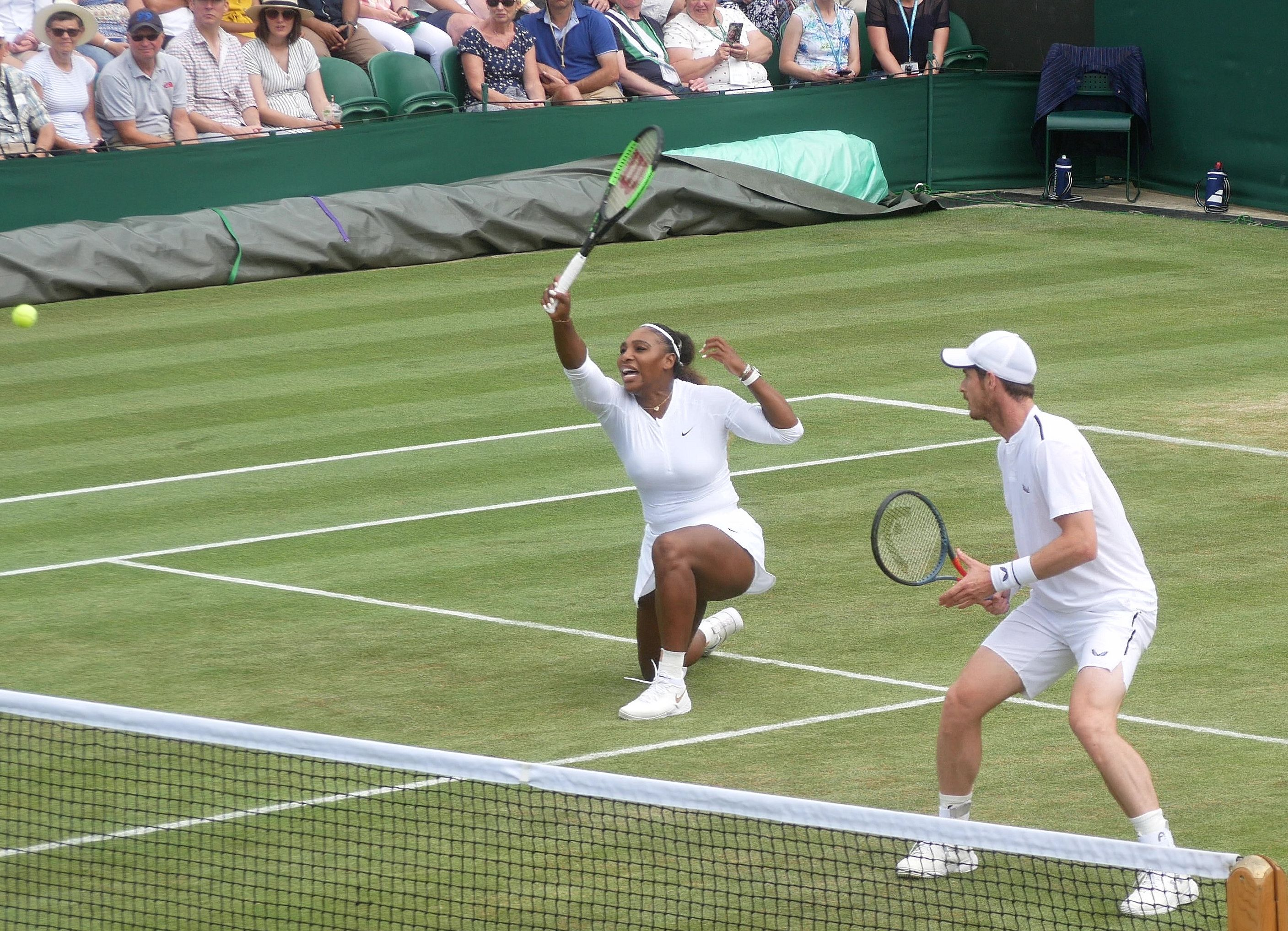 Serena Williams and her partner on the court caught in motion in their white outfits and they look amazing.