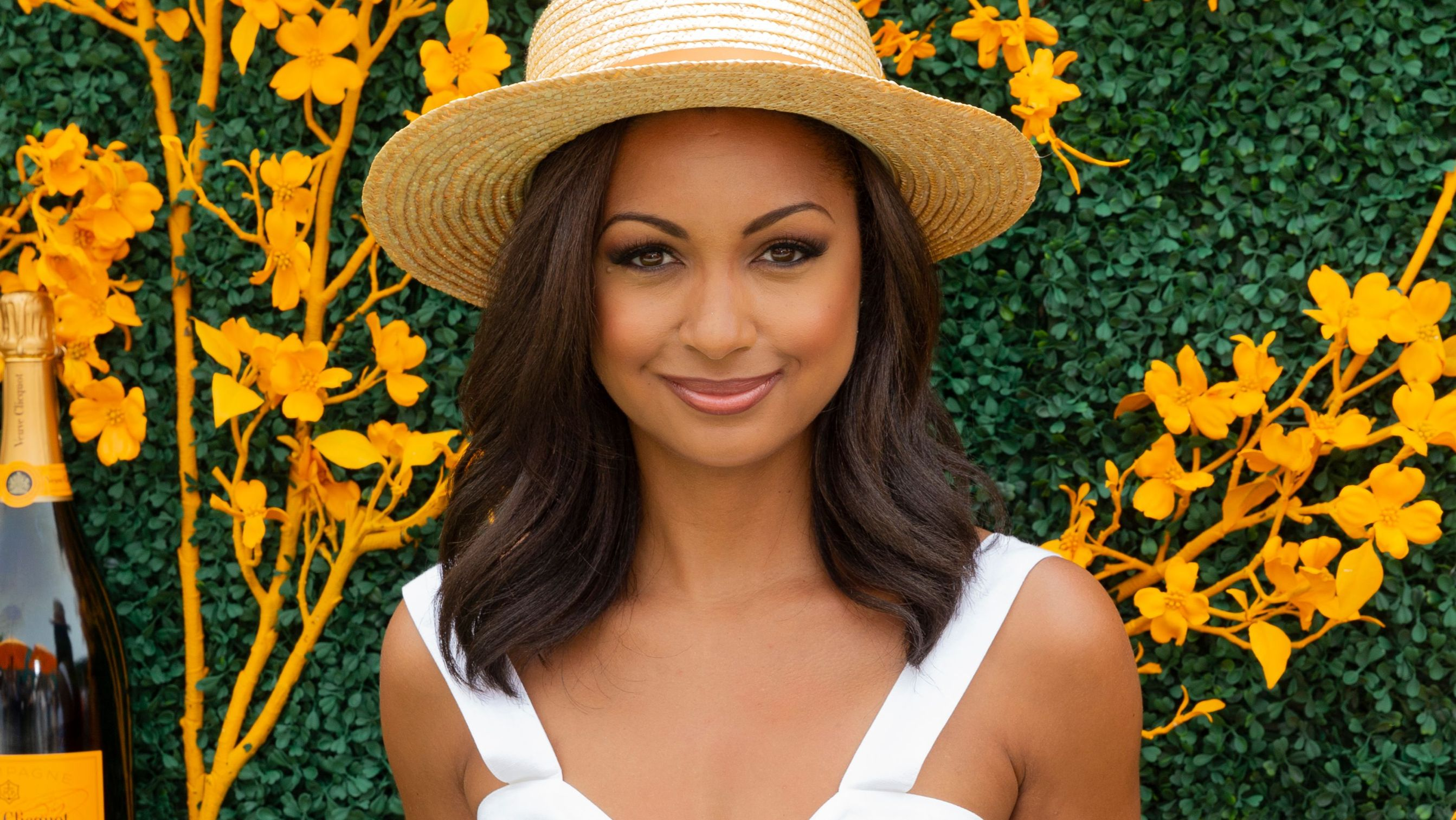 Eboni K. Williams wears a straw hat and white top.