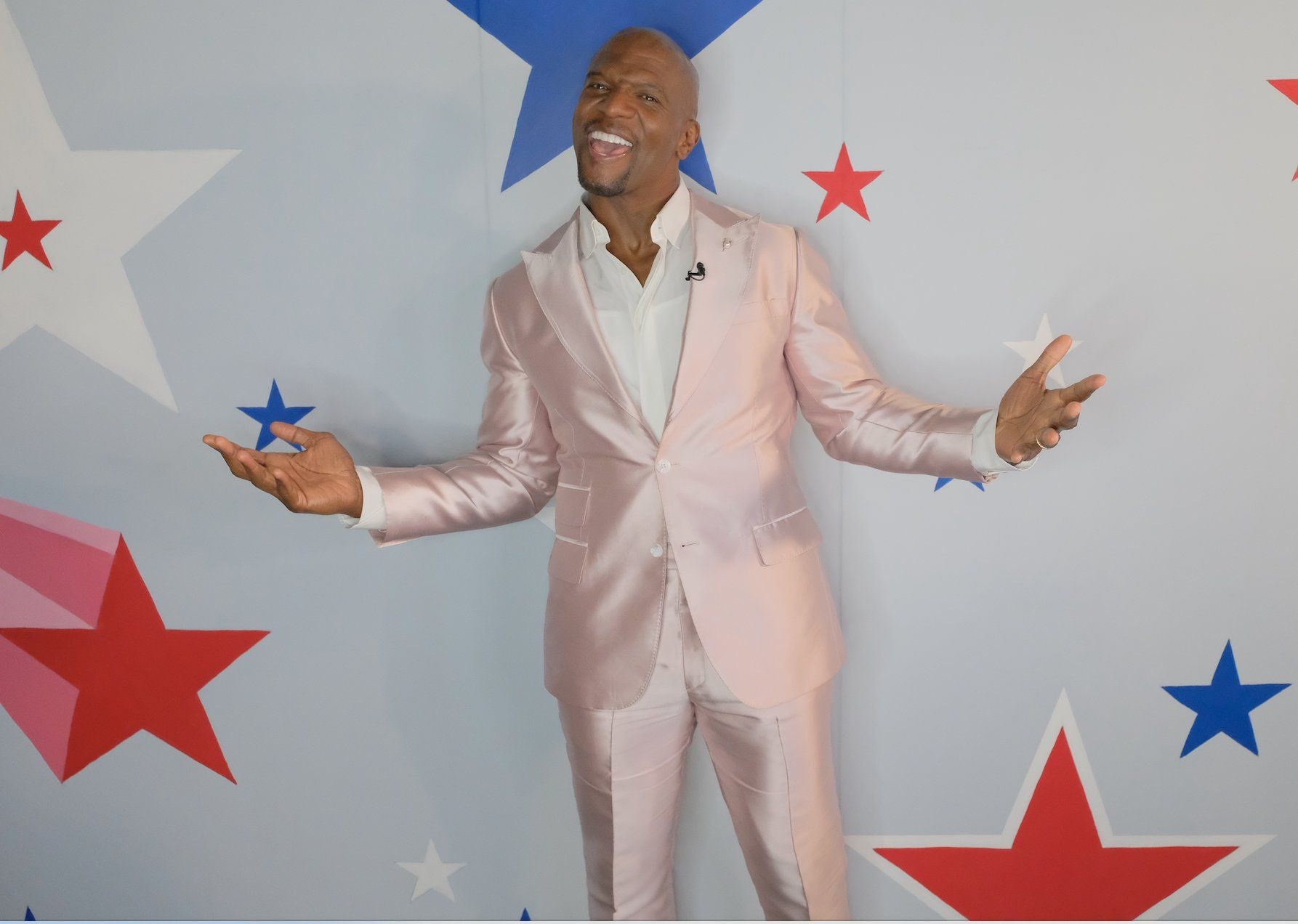 An amazing photo showing jolly Terry Crews in a pink two-piece suit and white T-shirt.