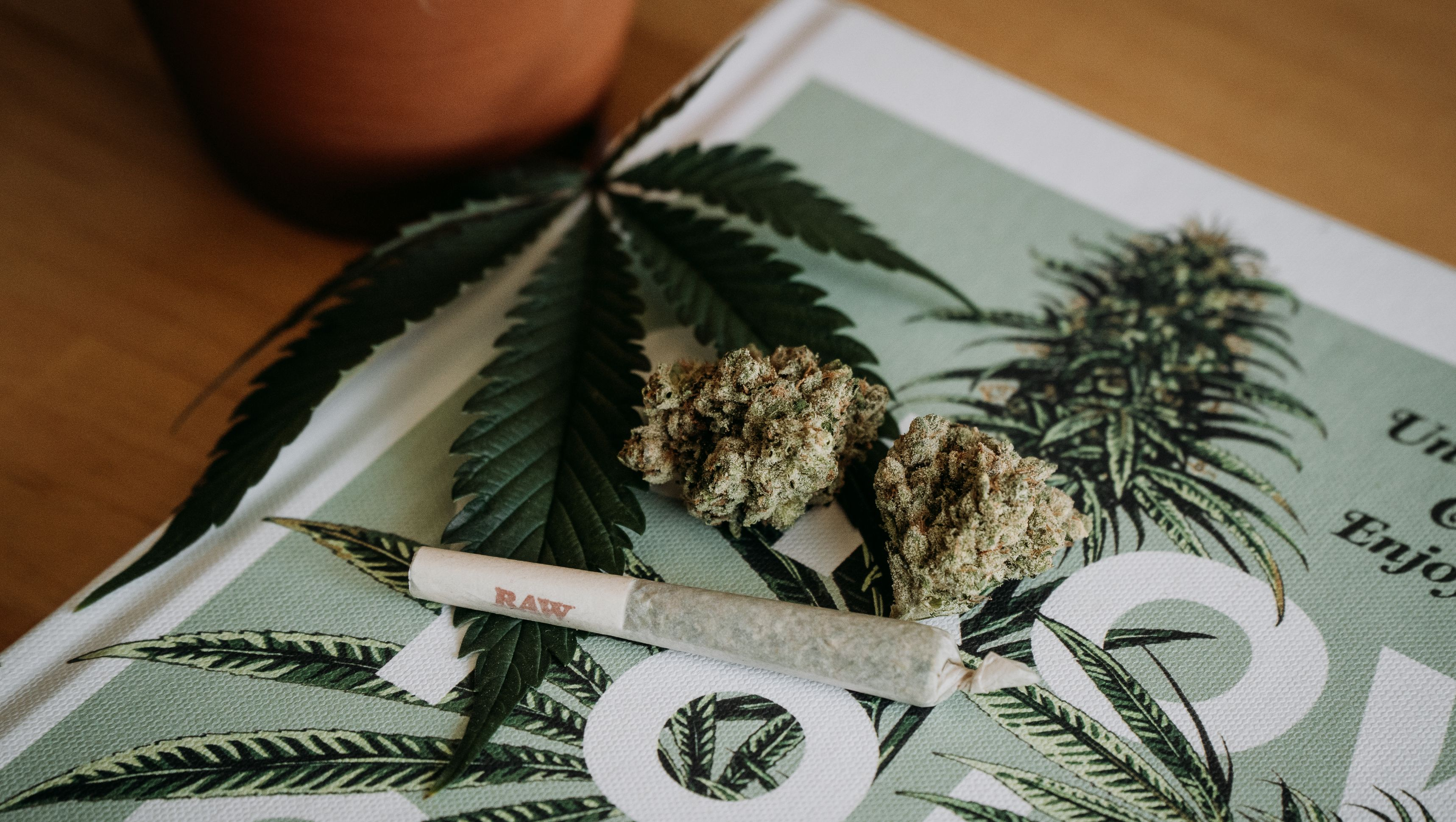 Marijuana leaf and joint on a table.
