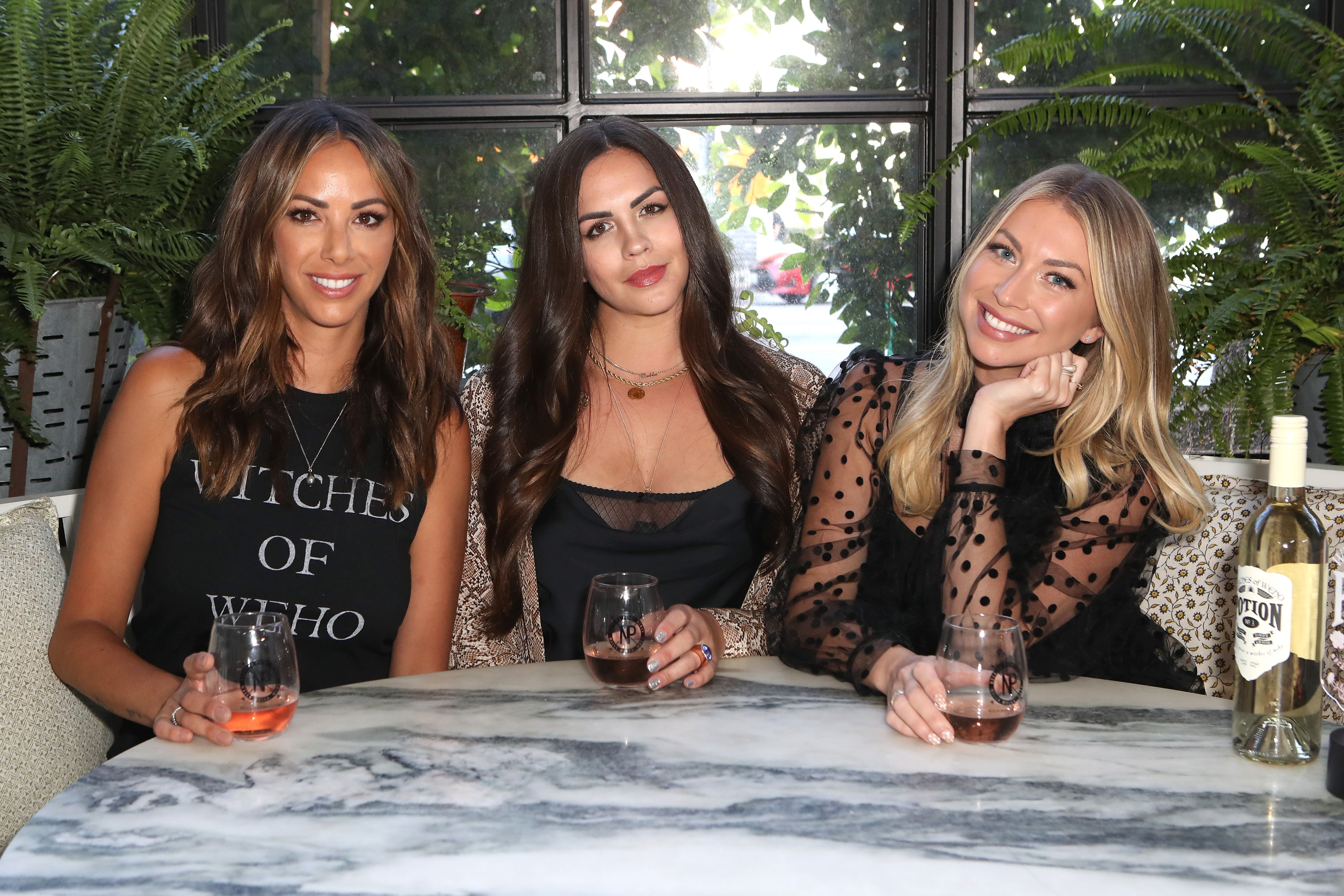 Kristen Doute (left), Katie Maloney-Schwartz (middle) and Stassi Schroeder (right) sit holding glasses of wine