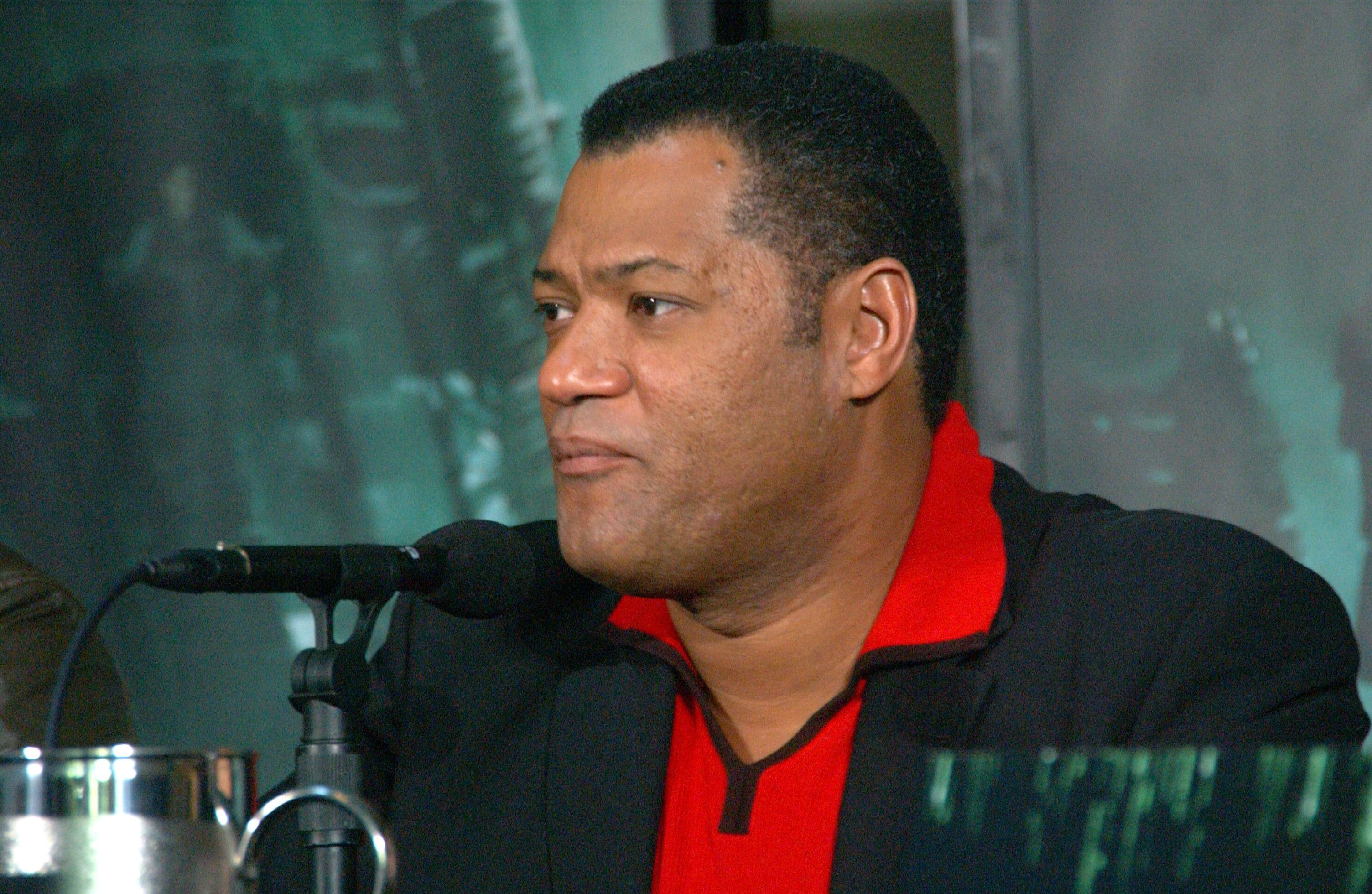Laurence Fishburne in front of a black and green Matrix-style background