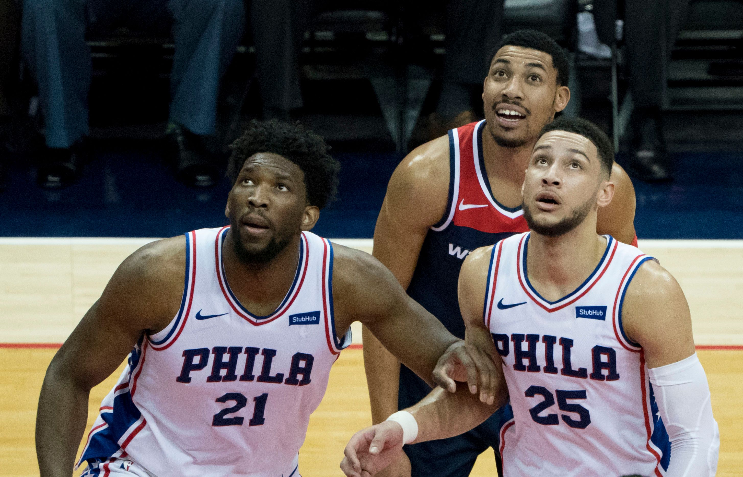 Joel Embiid and Ben Simmons block out a Washington Wizards player.