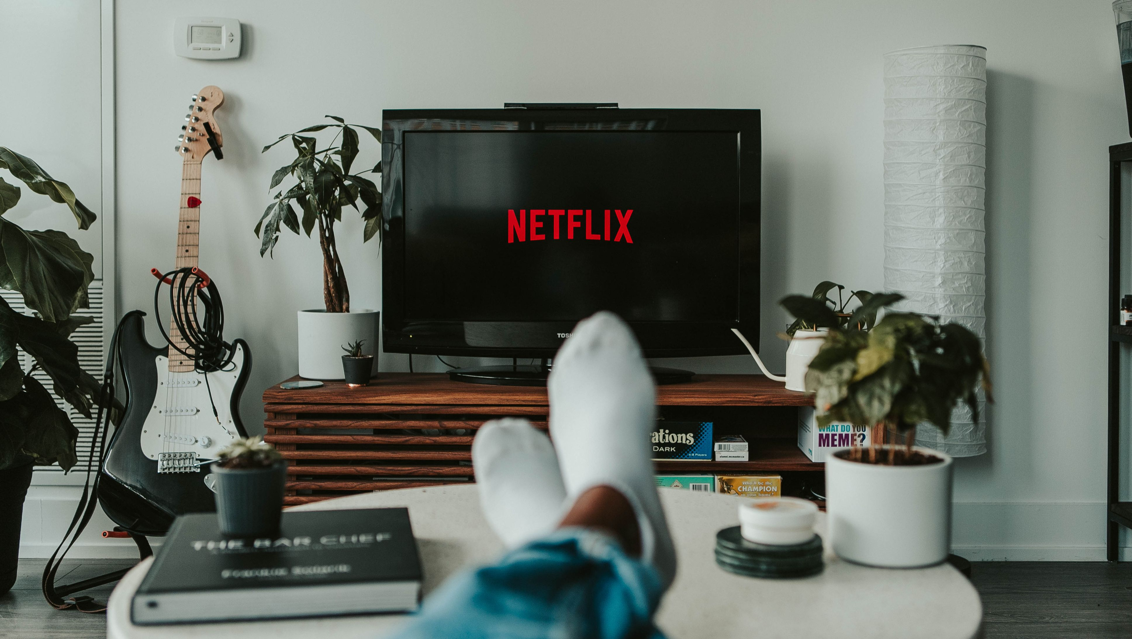 A pair of feet are seen in front of a TV with Netflix streaming.