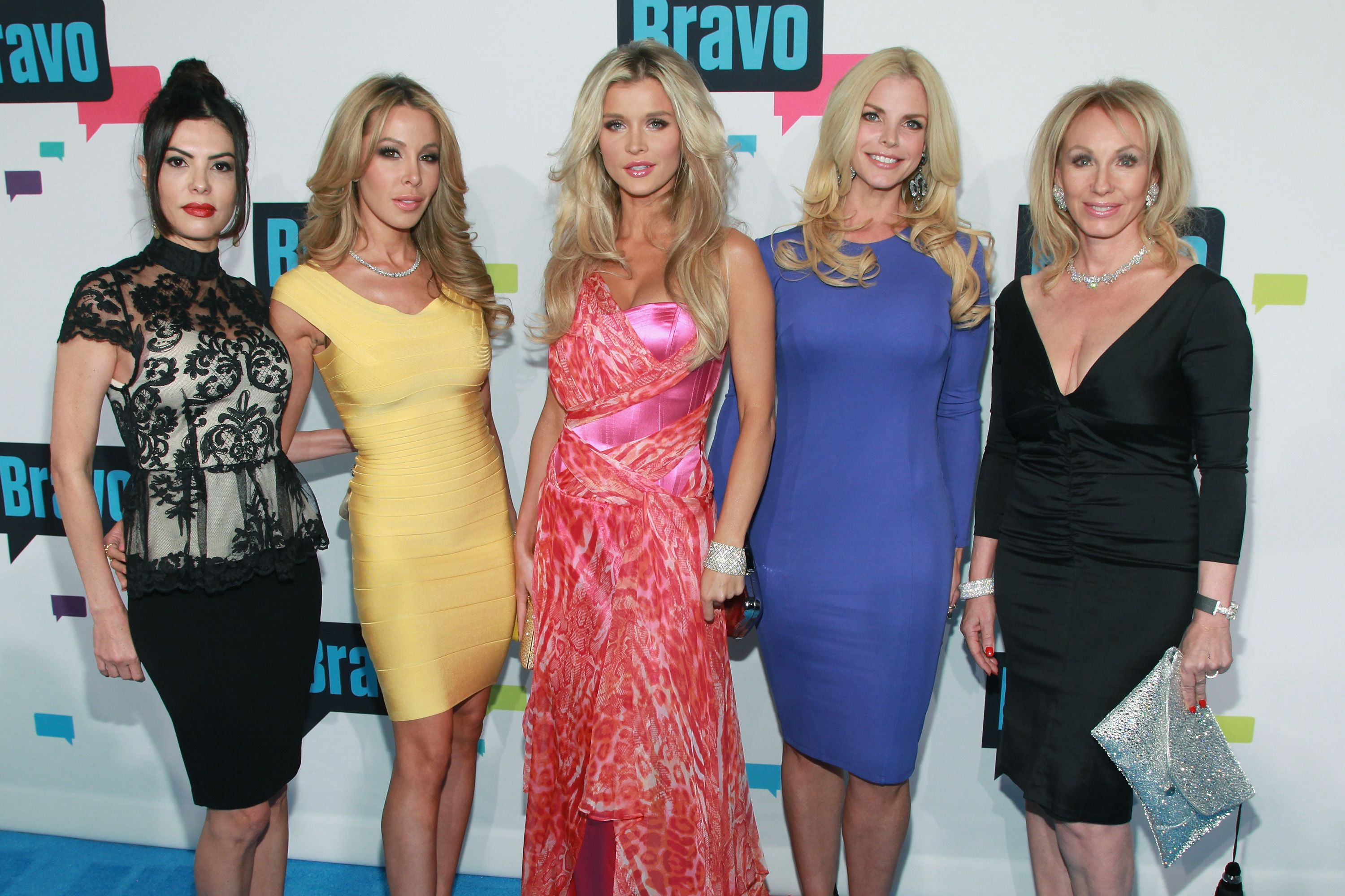 A group of women in different color dresses smiling at the camera.