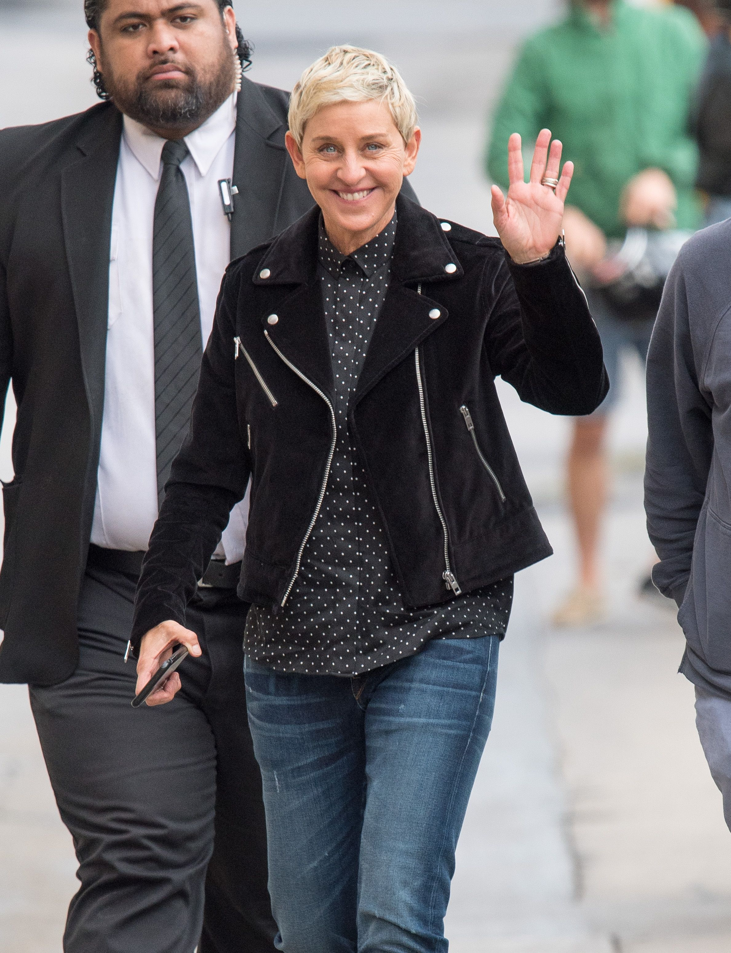 A lovely photo showing Ellen DeGeneres waving at a someone on the street and she has on a polka dot button-down shirt with a black jacket and blue denim pant.