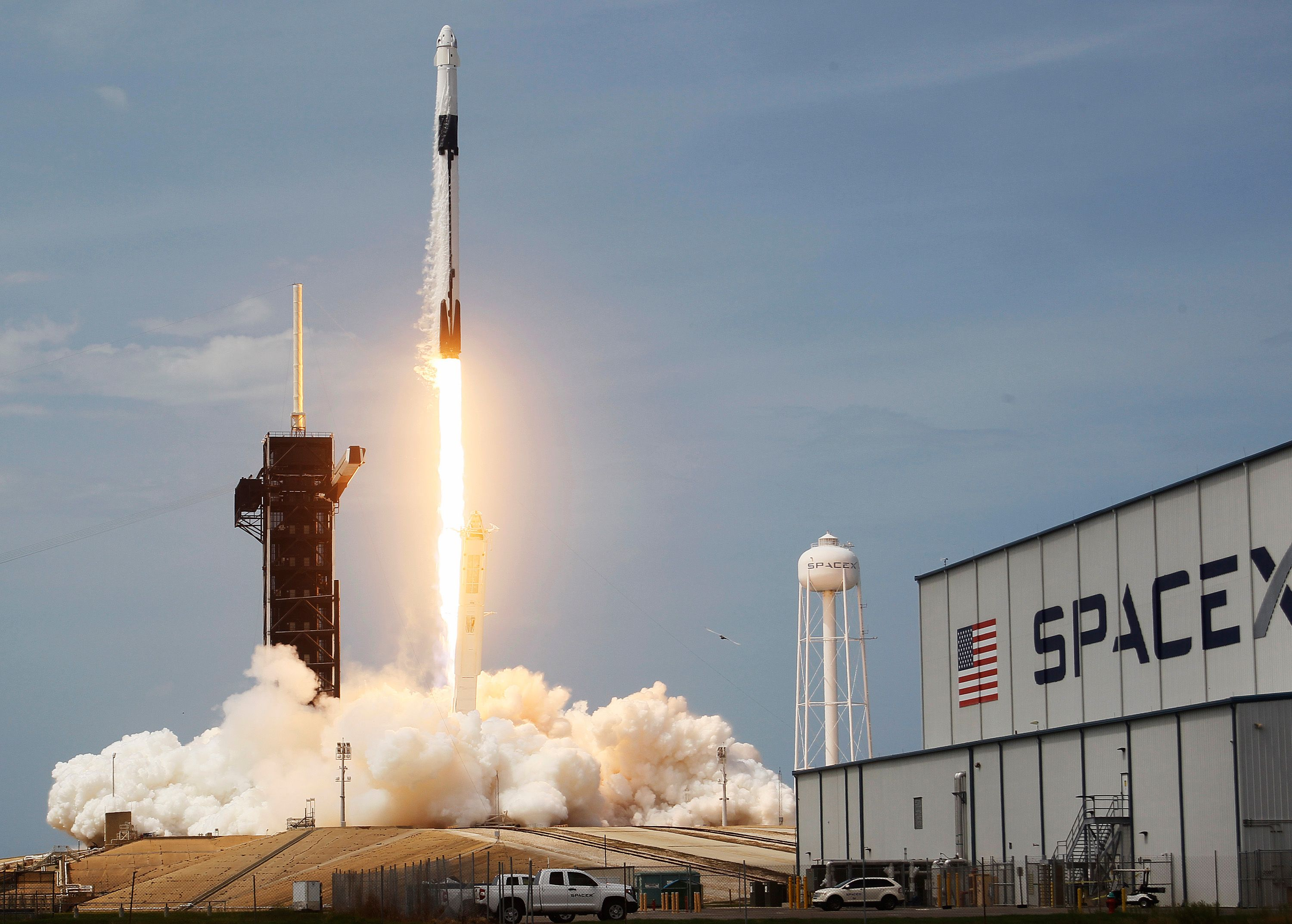 A SpaceX rocket launches upwards against a pale blue sky.