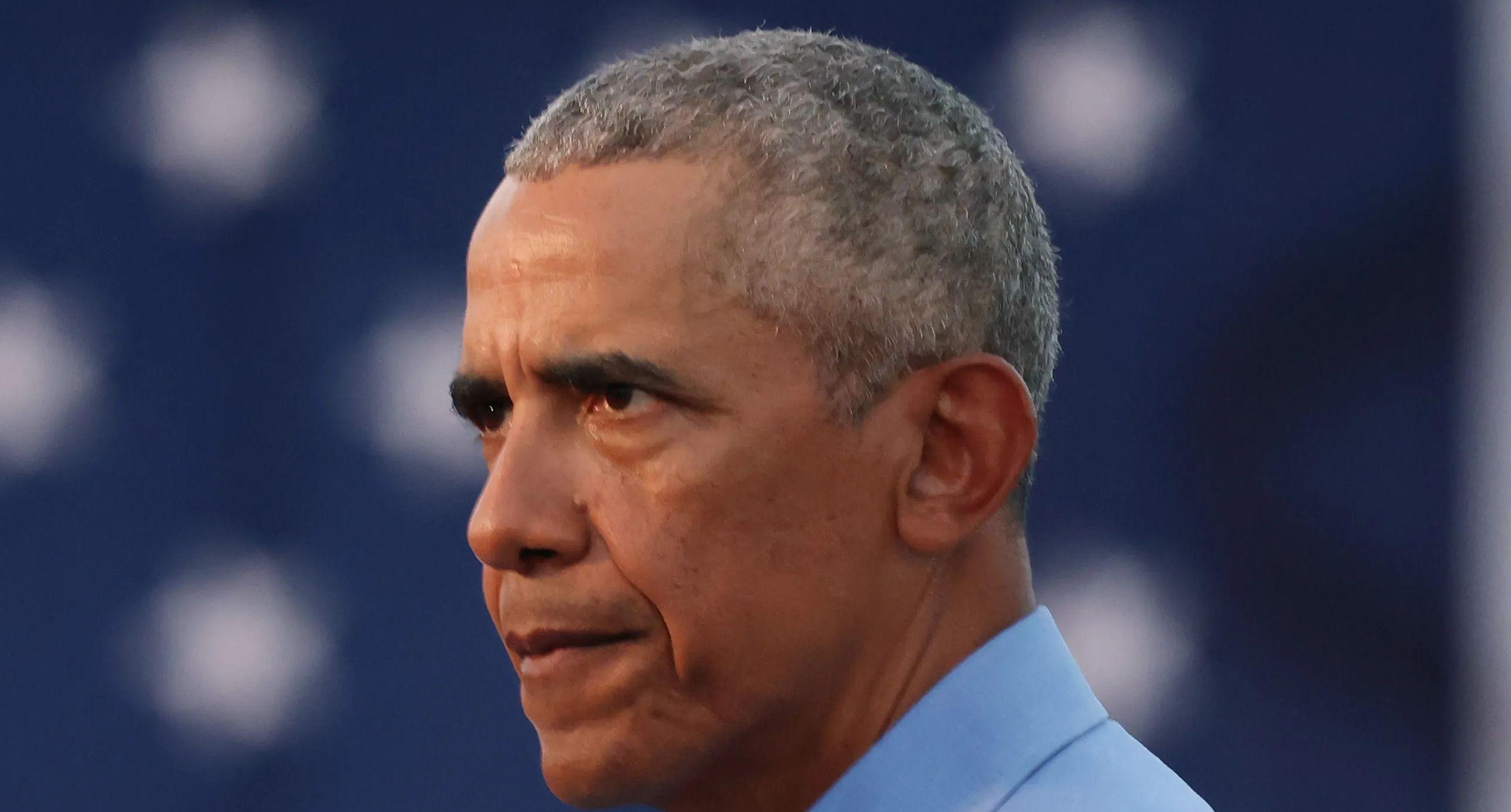 Former President Barack Obama looks on.