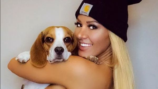 Kindly Myers poses with a dog
