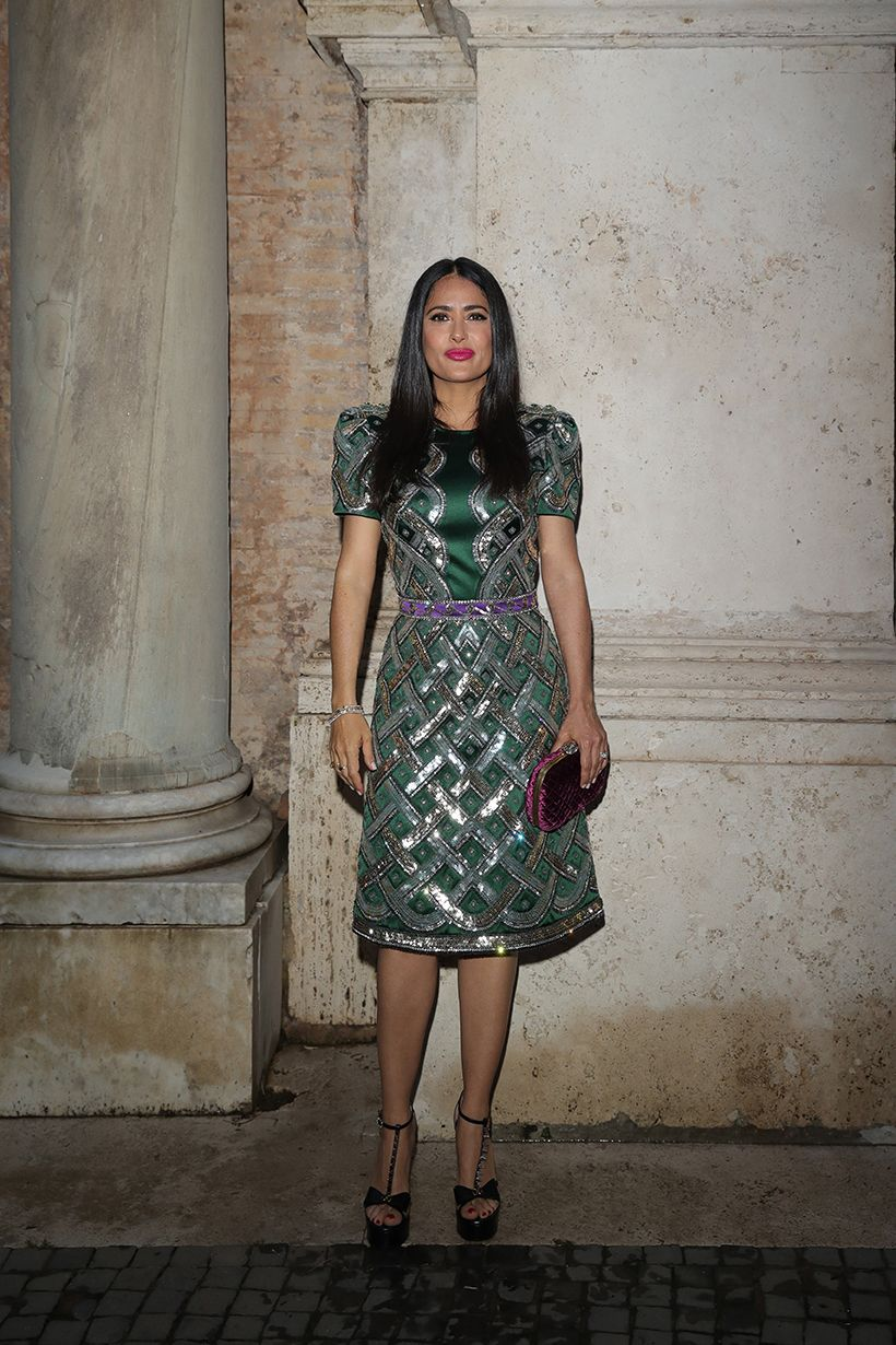 Salma Hayek Stubbs in this green shiny knee-length dress with a pink clutch and black sandals heel to match.