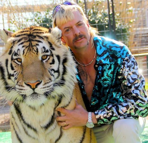 Joe Exotic poses for a photo with a tiger.