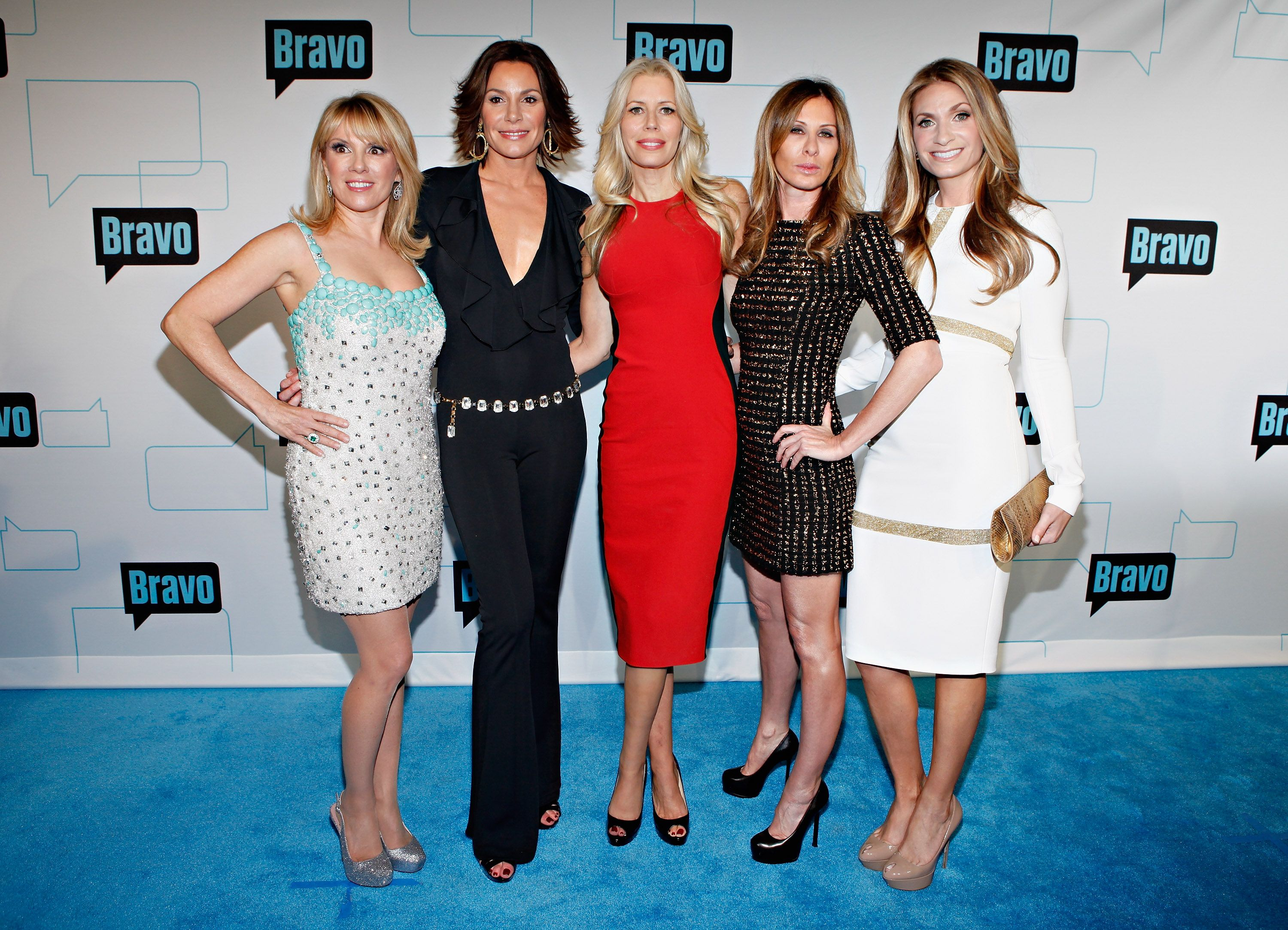 The 'RHONY' cast wears dresses and stands on a blue carpet.
