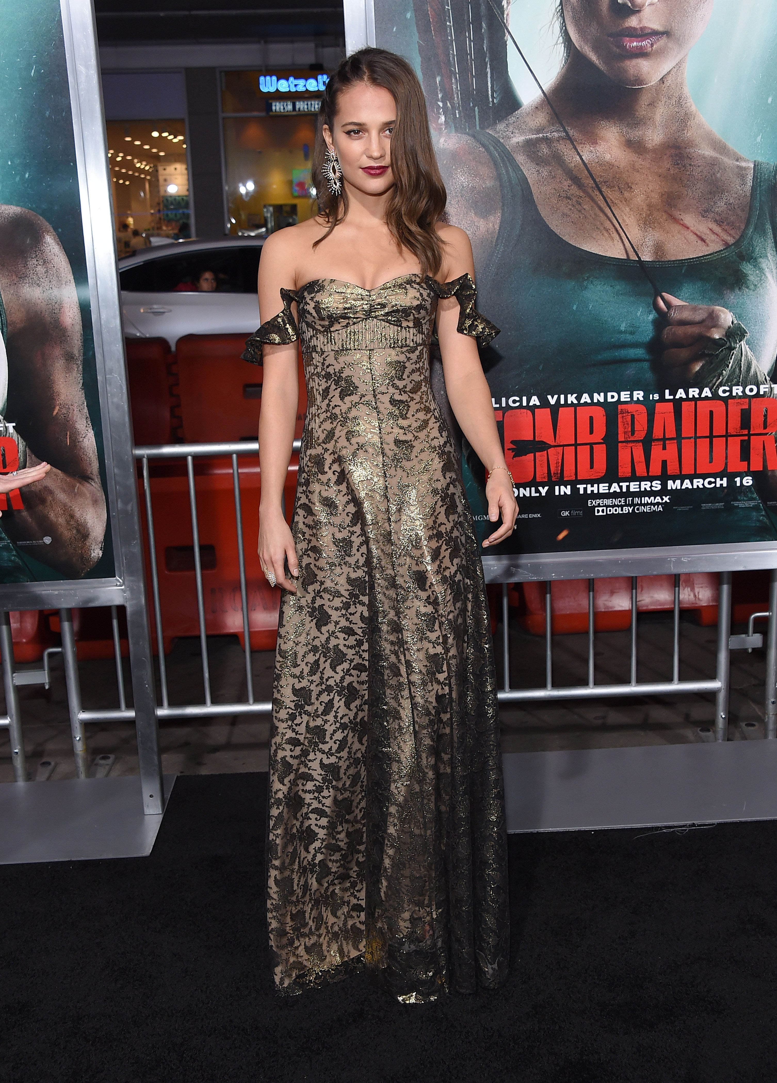 Alicia Vikander wears a printed dress in front of her 'Tomb Raider' billboard.