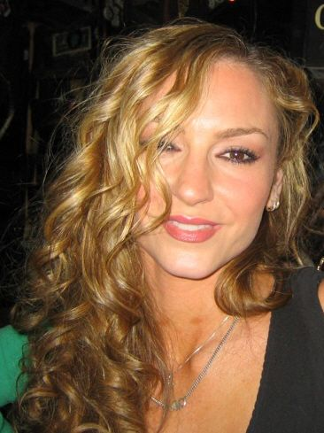 A blonde woman smiles into the camera.