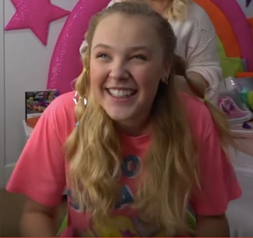 A blonde haired girl in pink smiles to the camera.