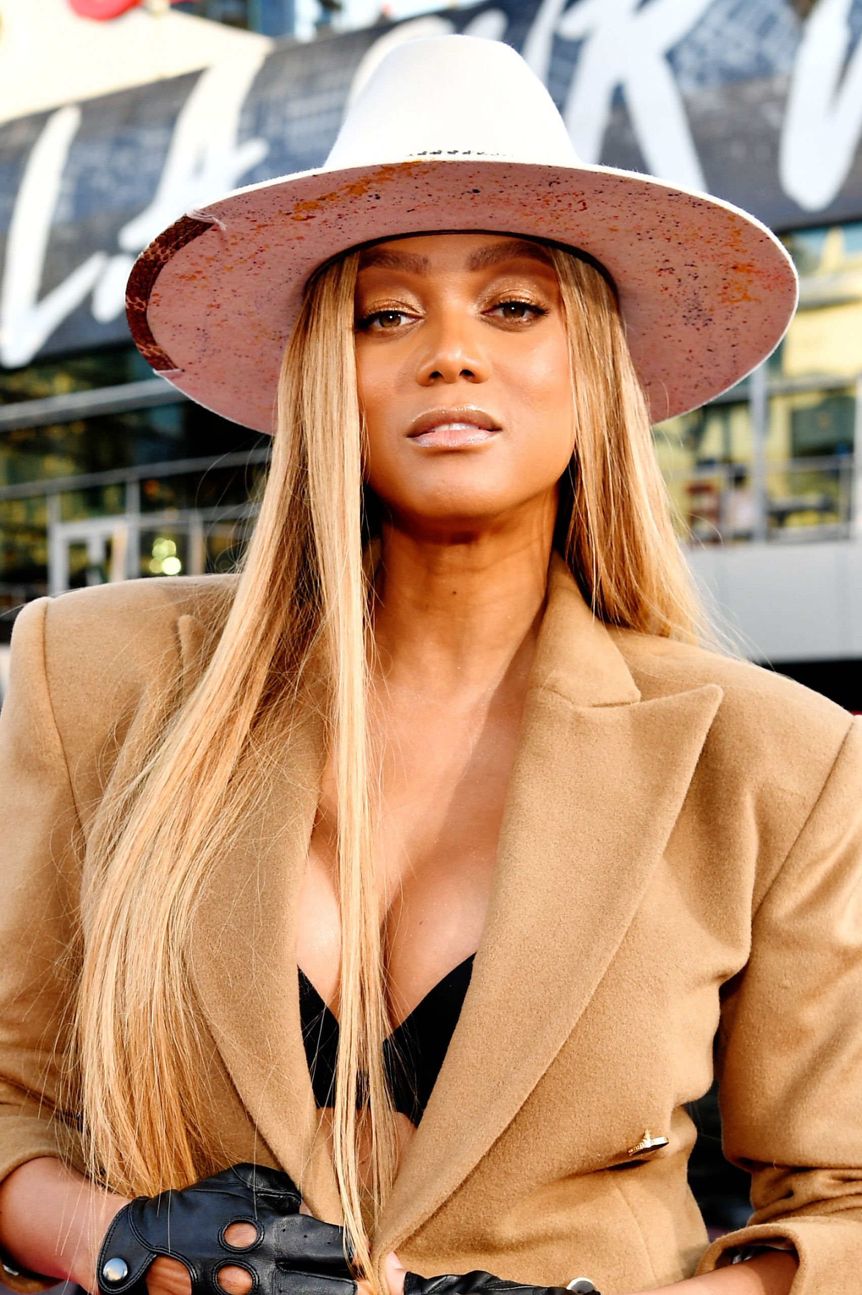 Tyra Banks poses wearing a hat and men's blazer