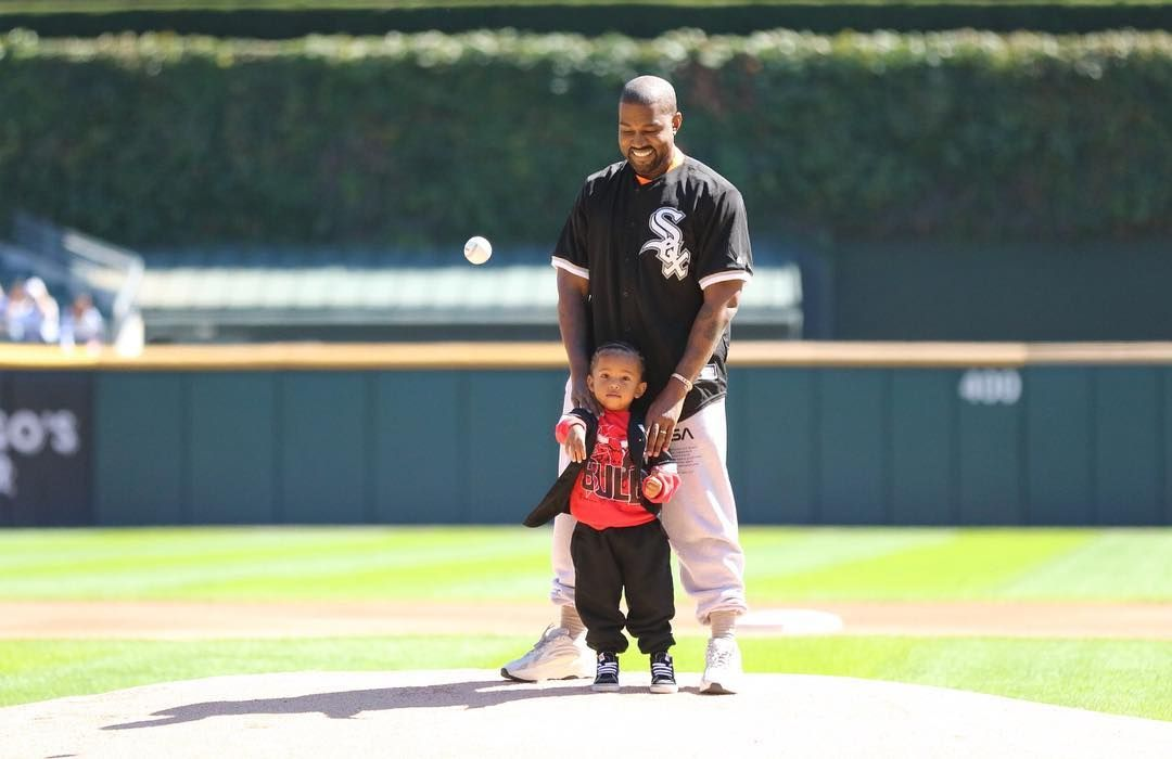 A photo of Kanye West having a father-son time on a large field.