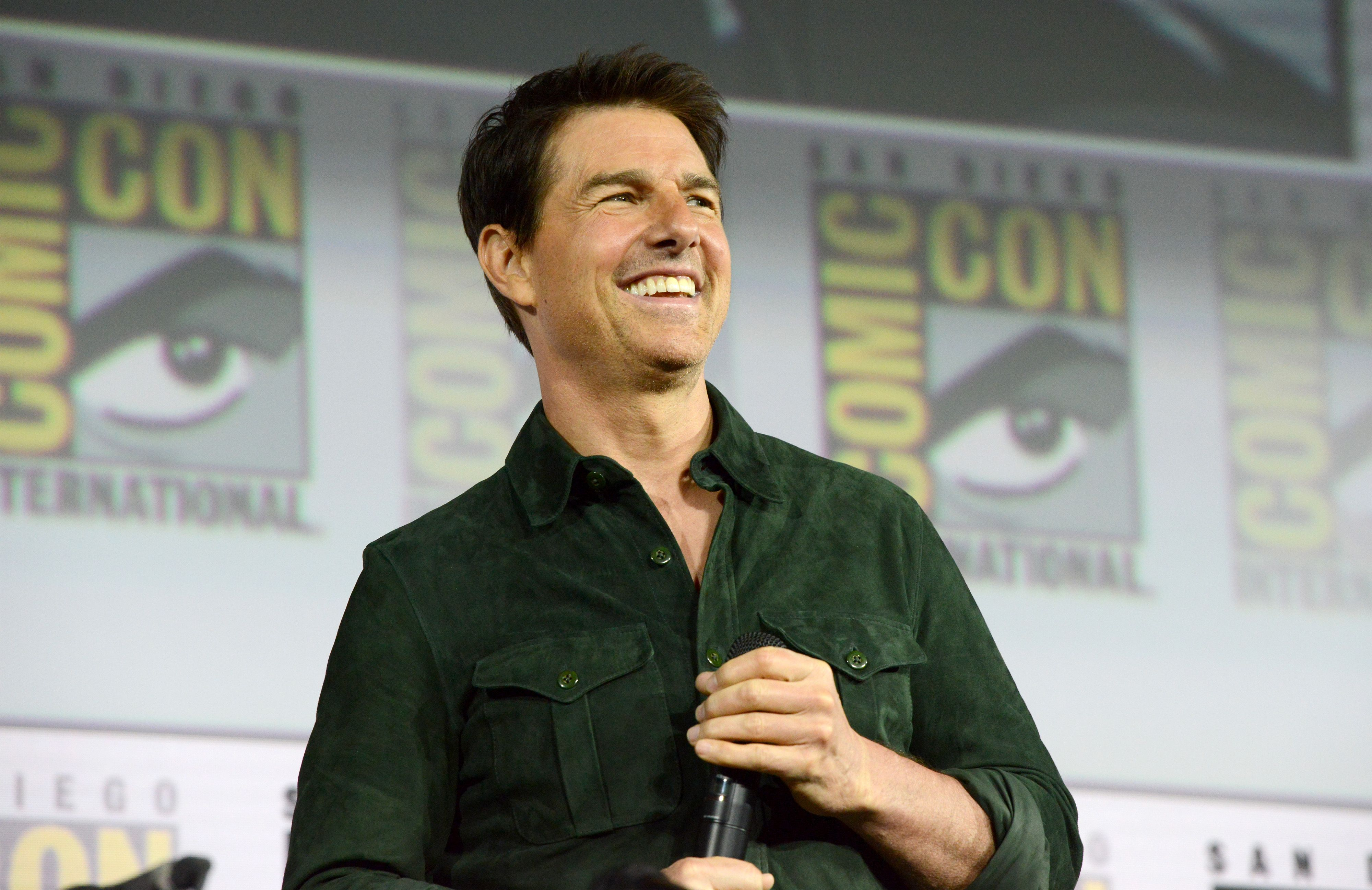Tom Cruise smiling and holding a microphone at Comic Con.