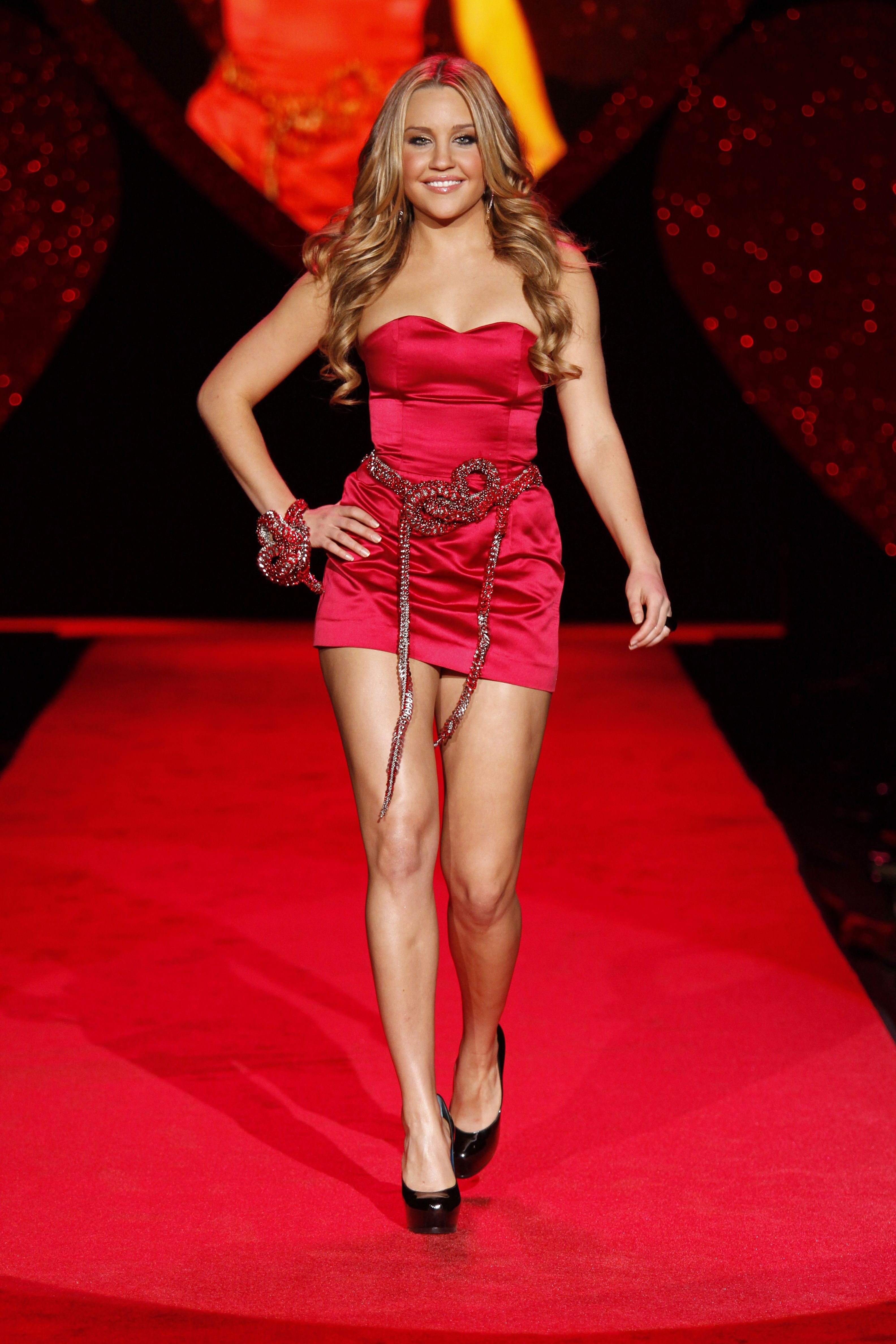 A photo showing Amanda Bynes walking down a red carpet dressed in a red low-cut dress and black heels.