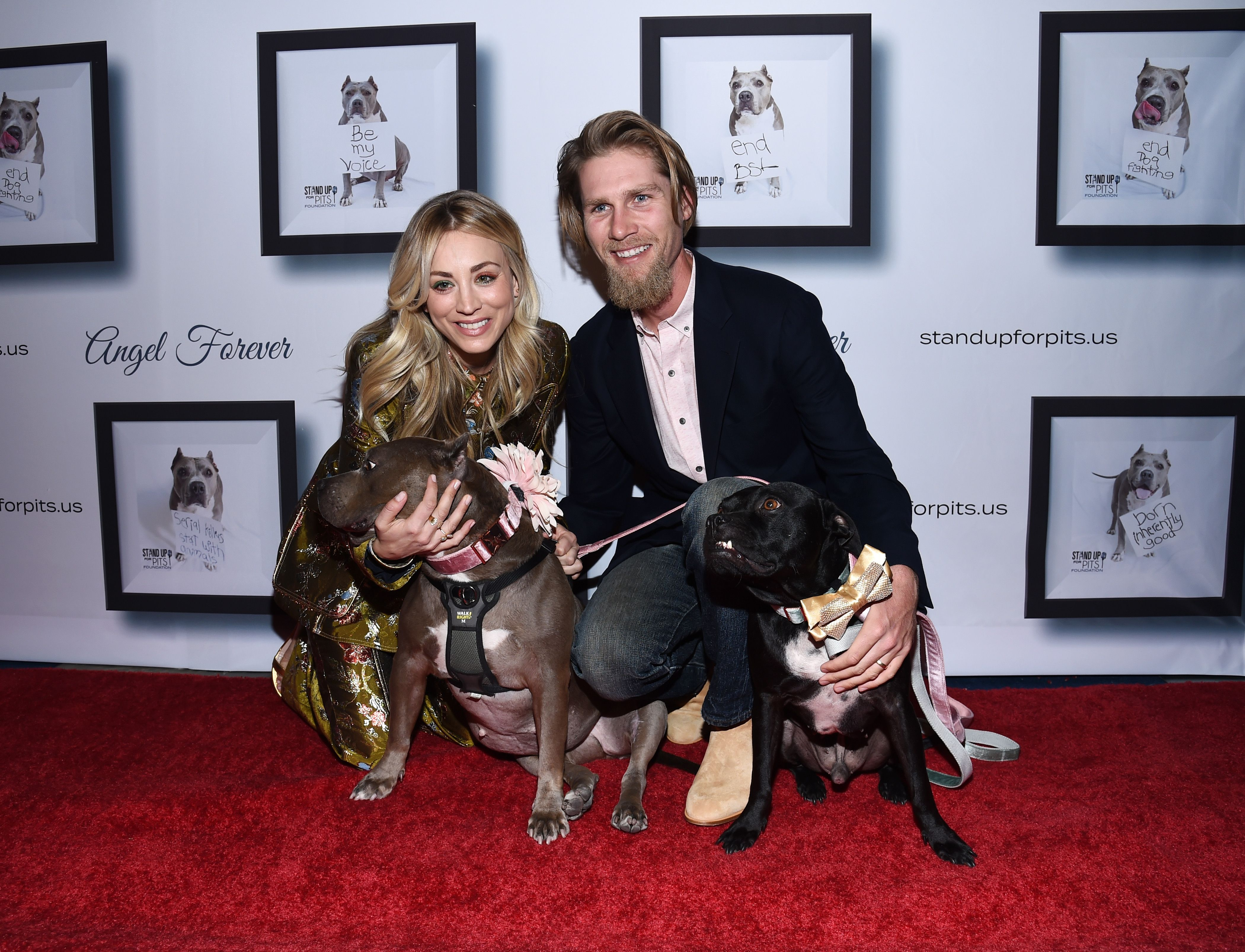 Kaley Cuoco and Karl Cook pose on the red carpet with their dogs