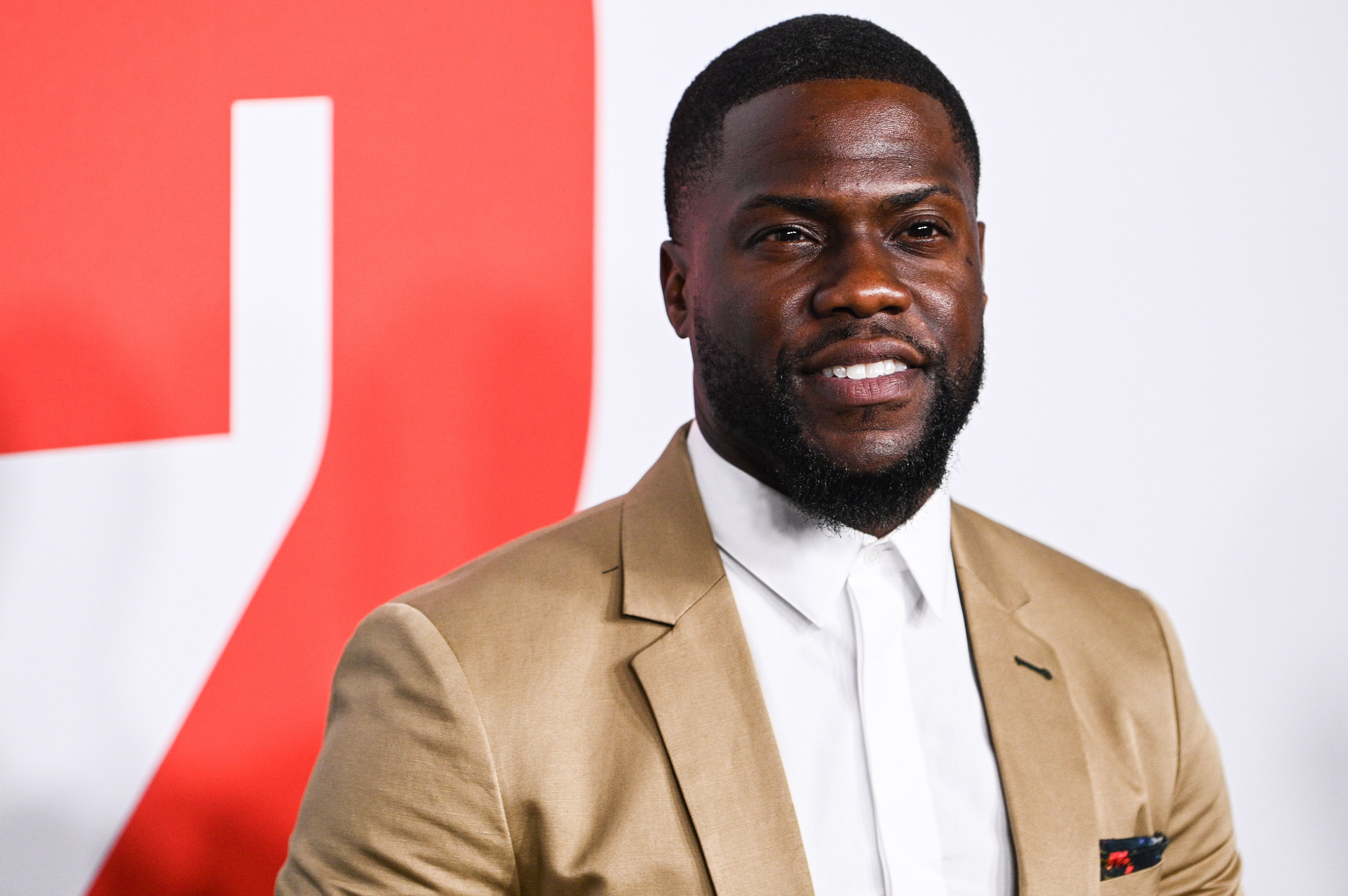 Kevin Hart looks amazing in this brown suit with a white inner T-shirt to match at an event.