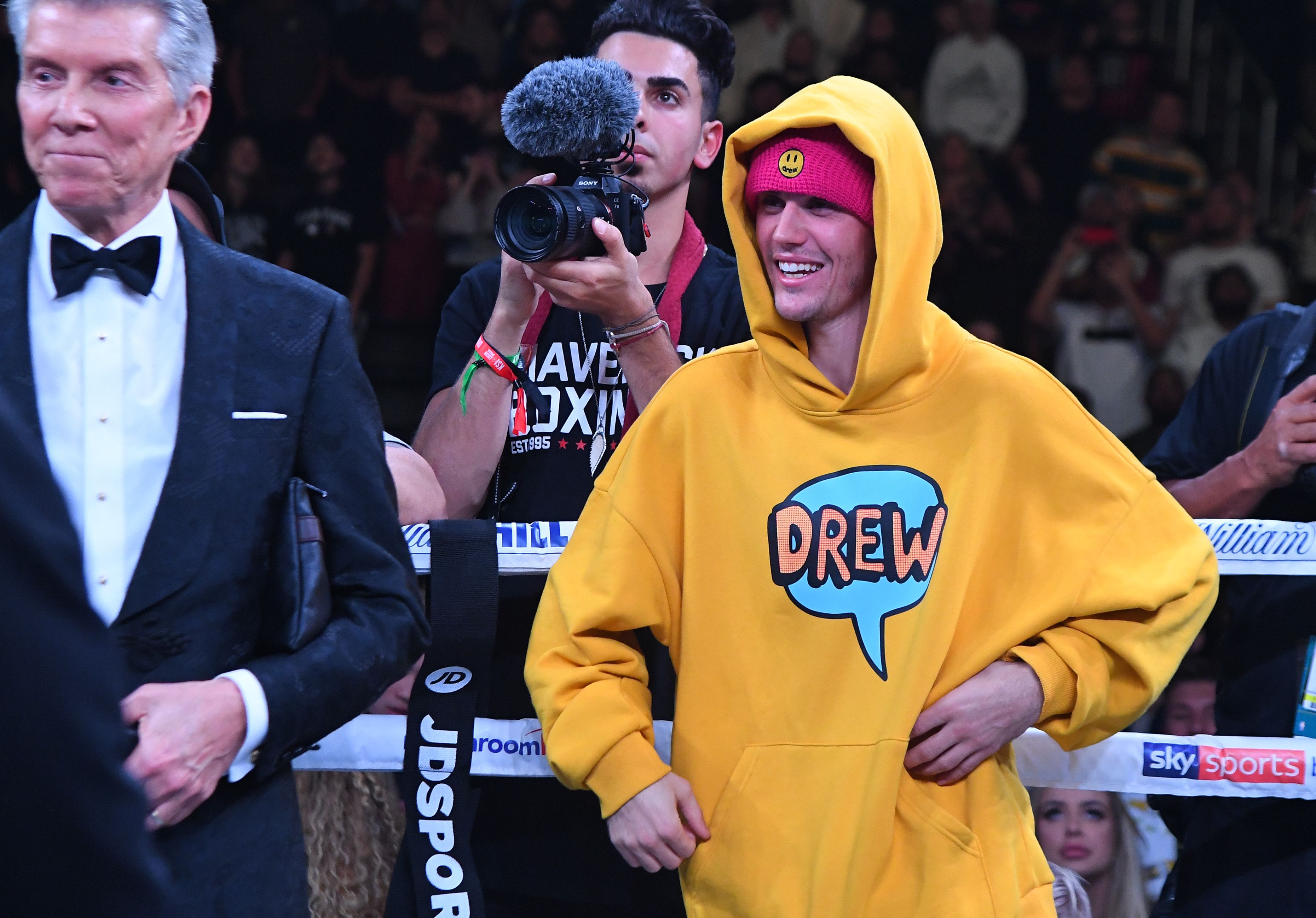 Justin Bieber wearing a yellow sweatshirt.