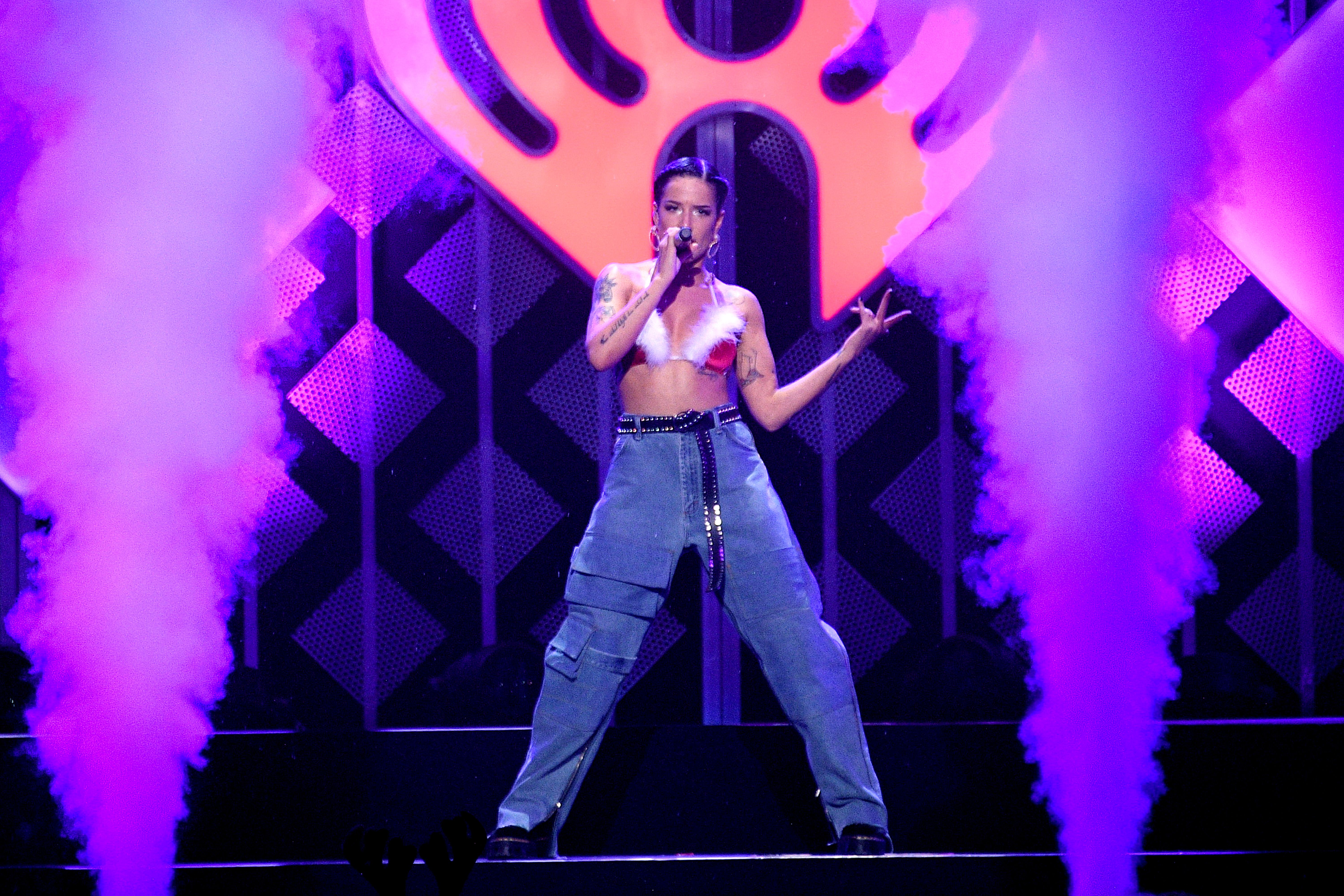 Halsey holds a microphone while posing on stage