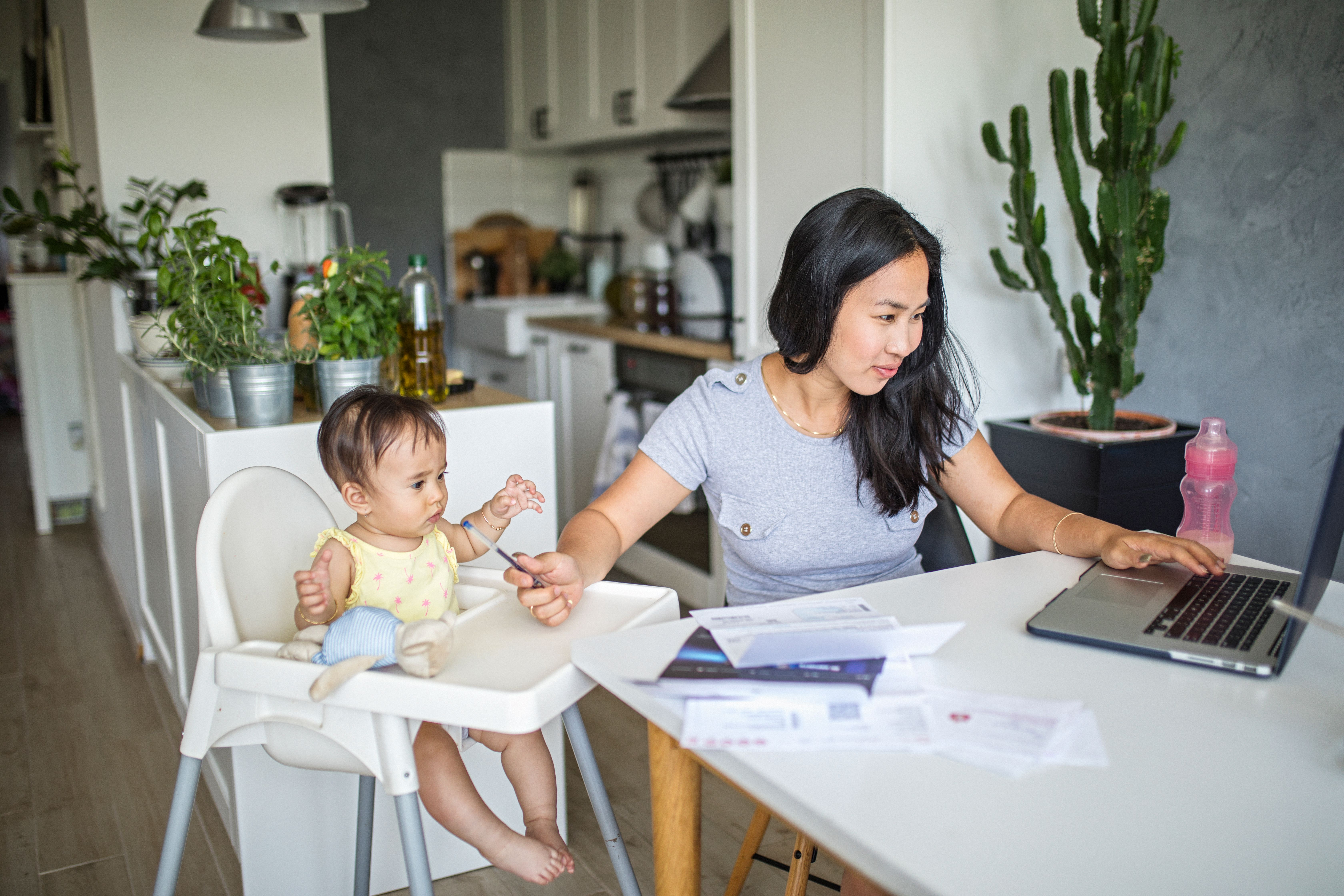 Woman working on a laptop while also feeding a child in a high chair