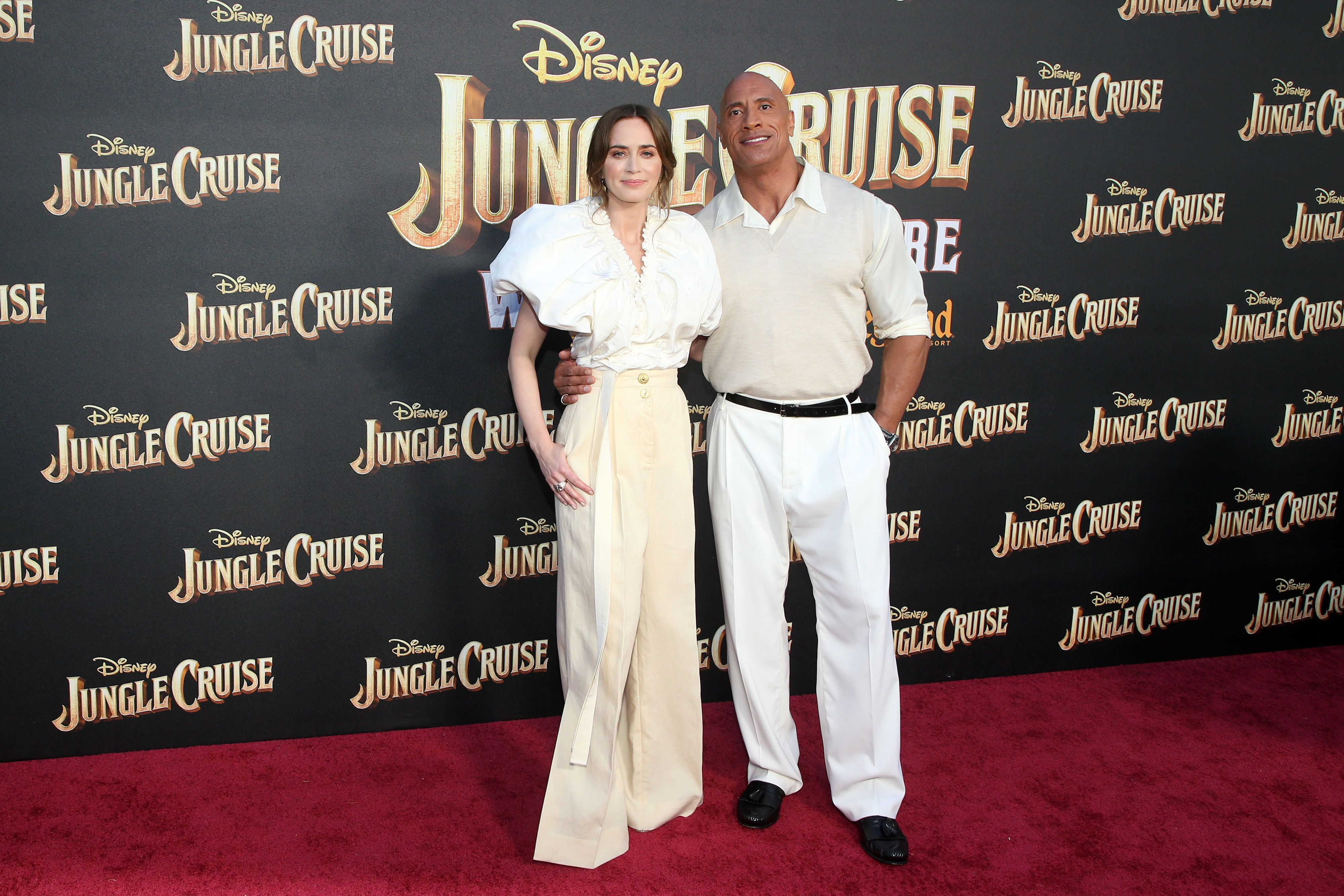 Emily Blunt and Dwayne 'The Rock' Johnson wear tan and white two-pieces on the red carpet.