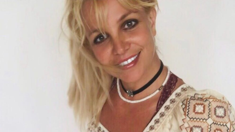 Britney Spears poses smiling in a pattern shirt