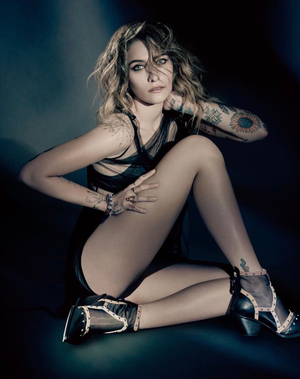 An amazing photo showing Paris Jackson sitting in a dark room, wearing a black lingerie and her legs crossed.