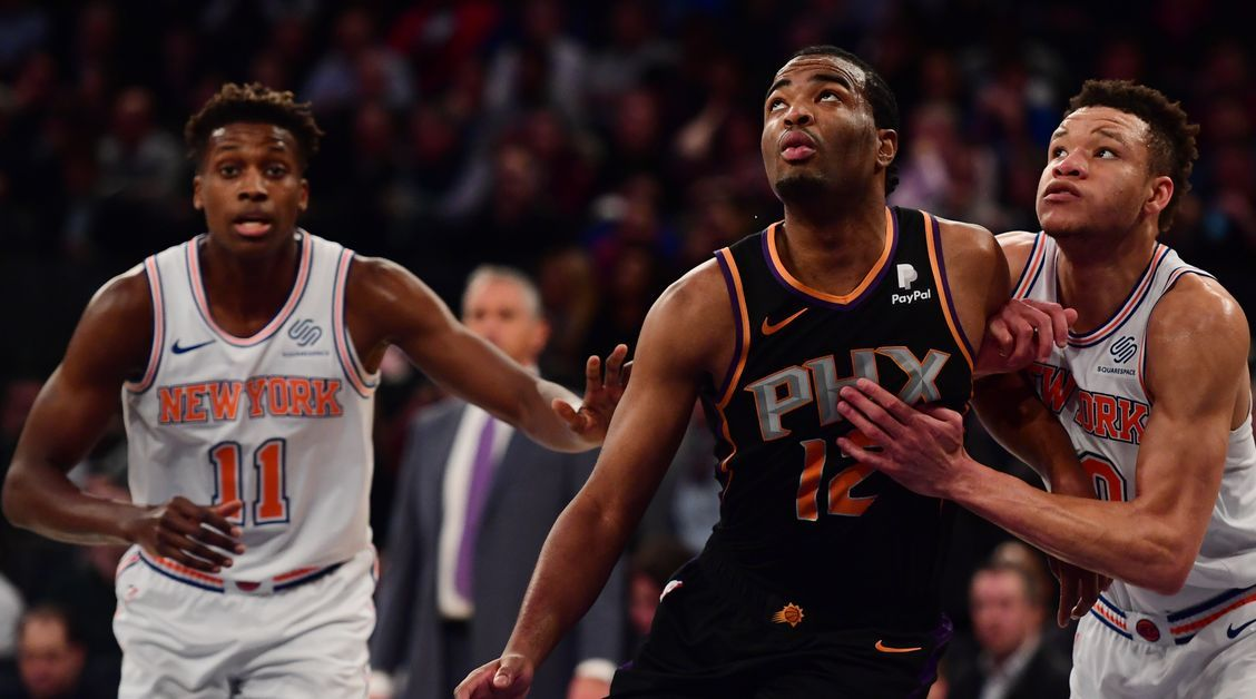 Frank Ntilikina, TJ Warren, and Kevin Knox battle for a rebound during a 2018 game between the New York Knicks and Phoenix Suns.