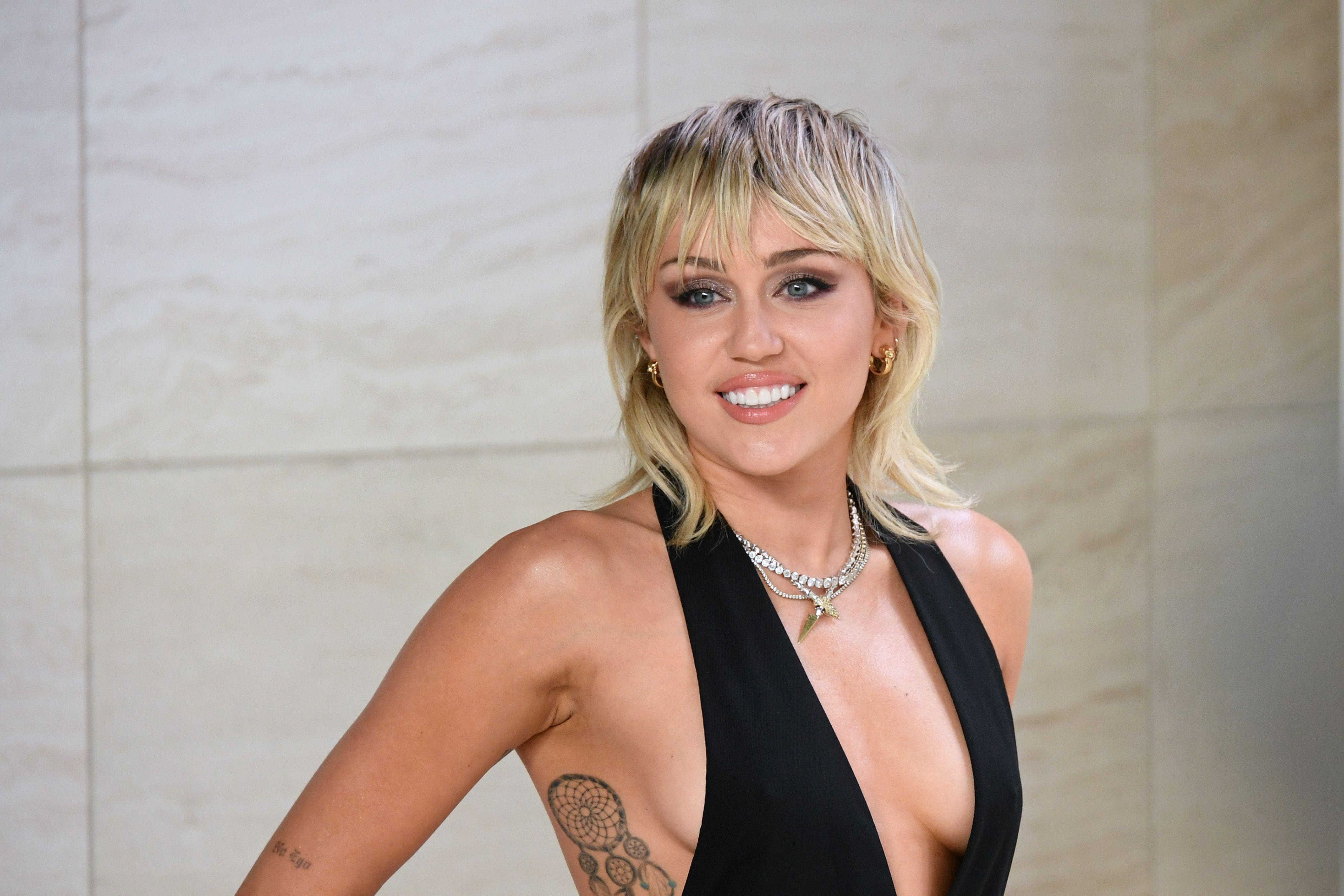 Miley Cyrus poses smiling at the camera