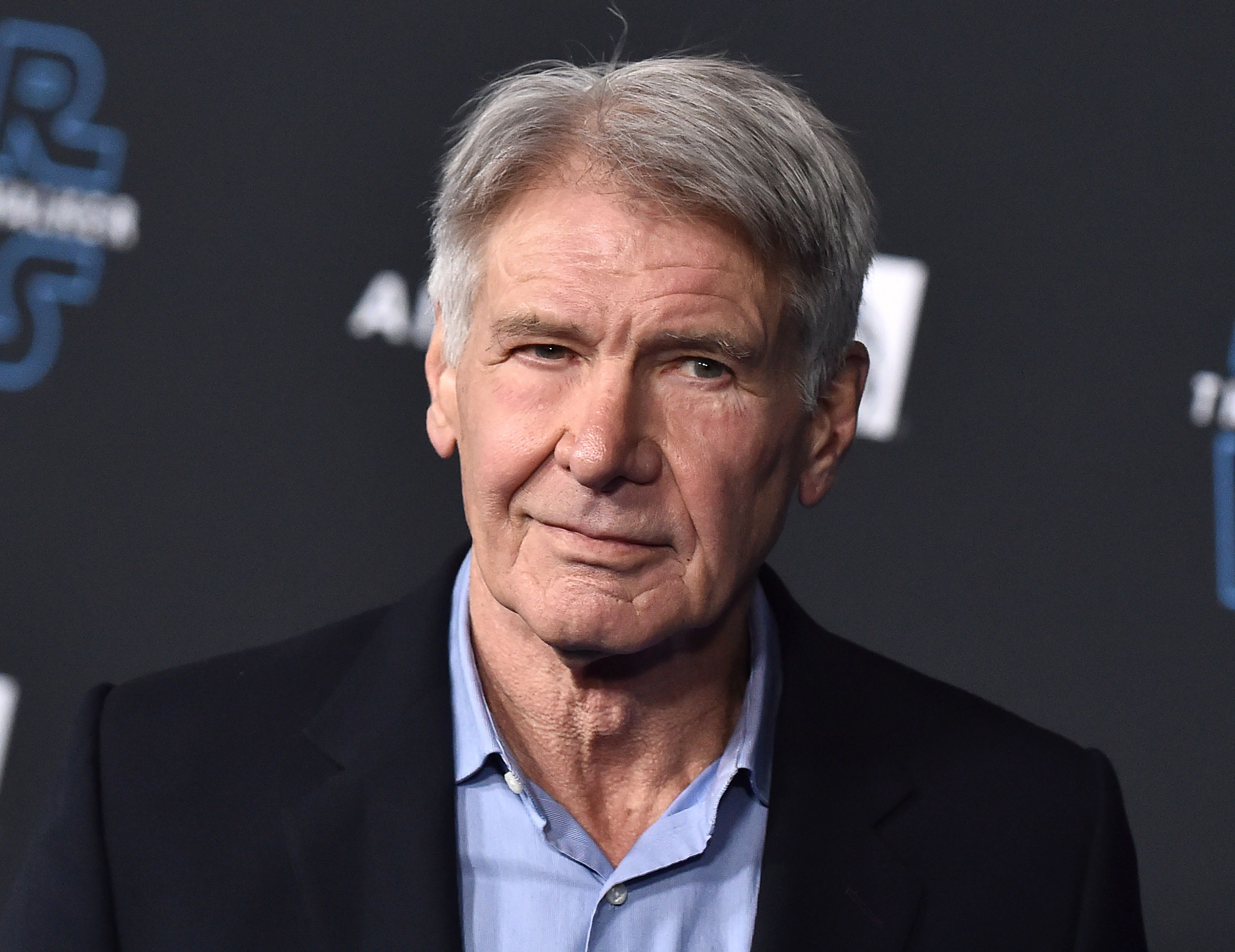 Harrison Ford wears a blue button up and black blazer.