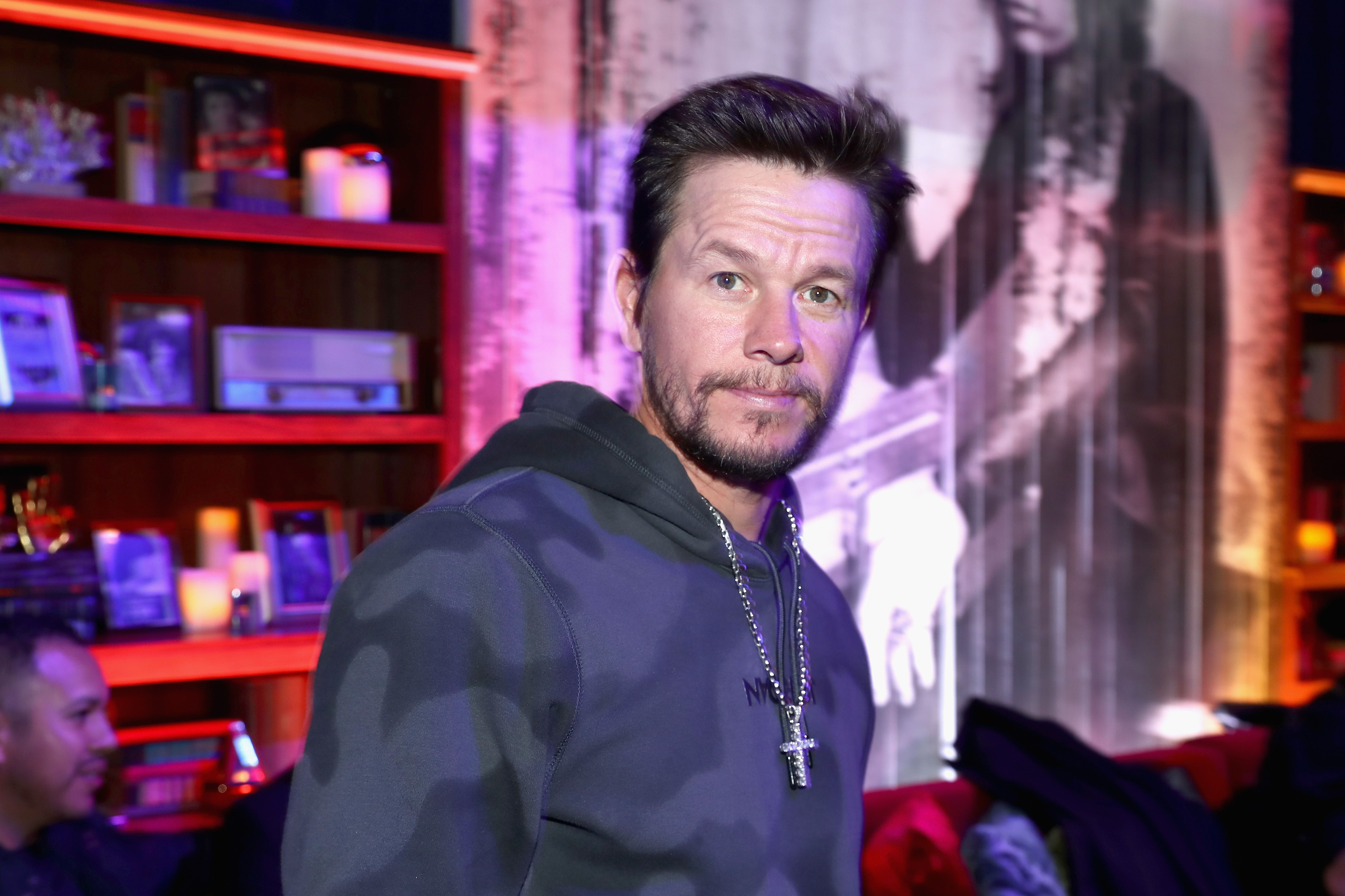 Mark Wahlberg wears a gray hoodie and silver cross.