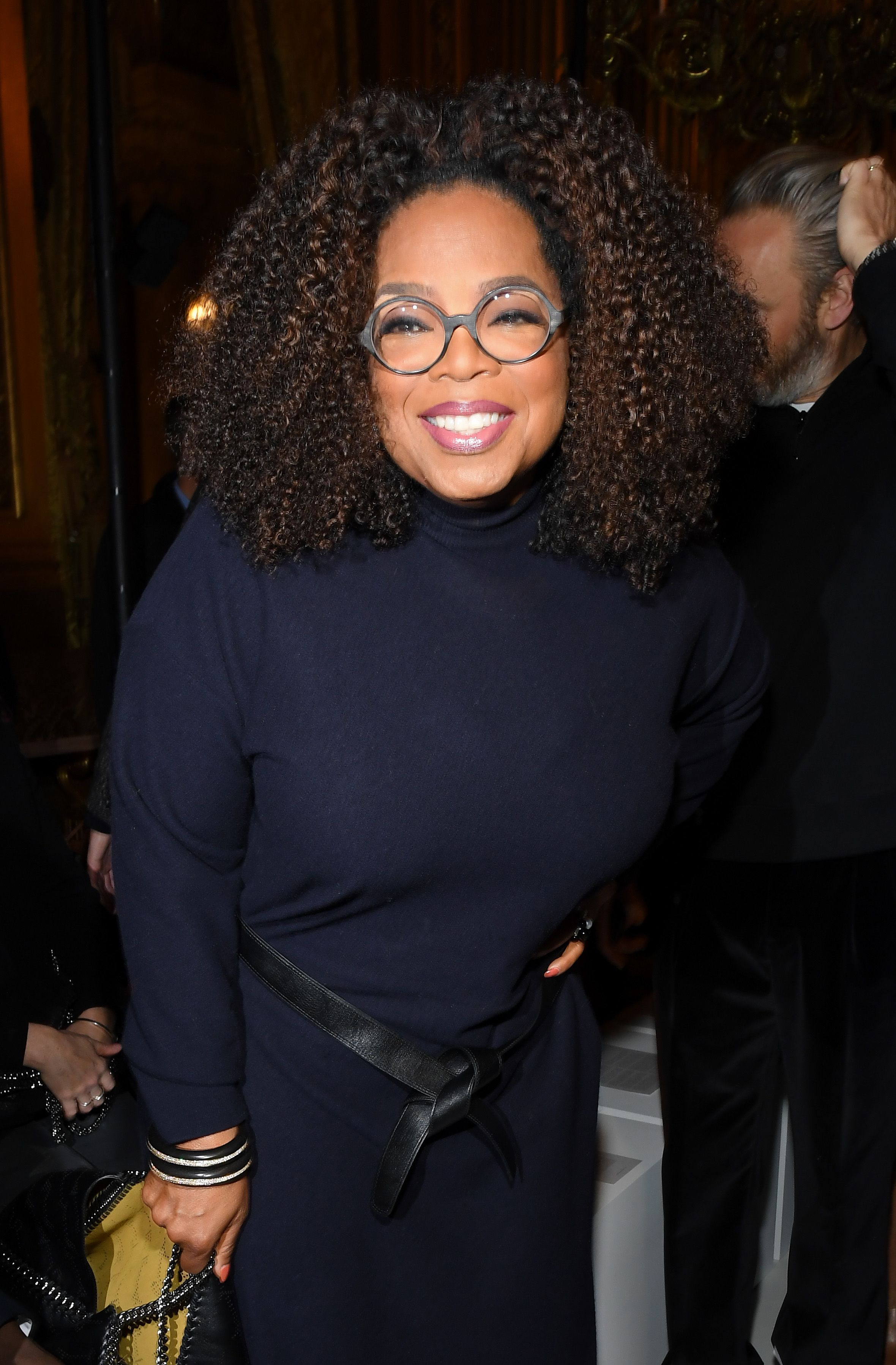 Oprah Winfrey poses beautifully for the camera in dark blue dress with a black stylish belt across her stomach.