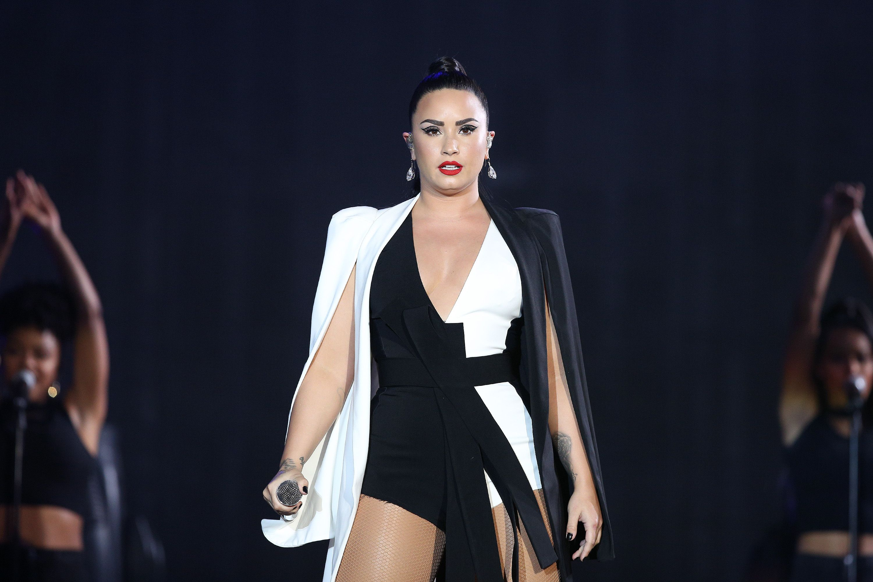 Demi Lovato dressed in black and white performs on stage.