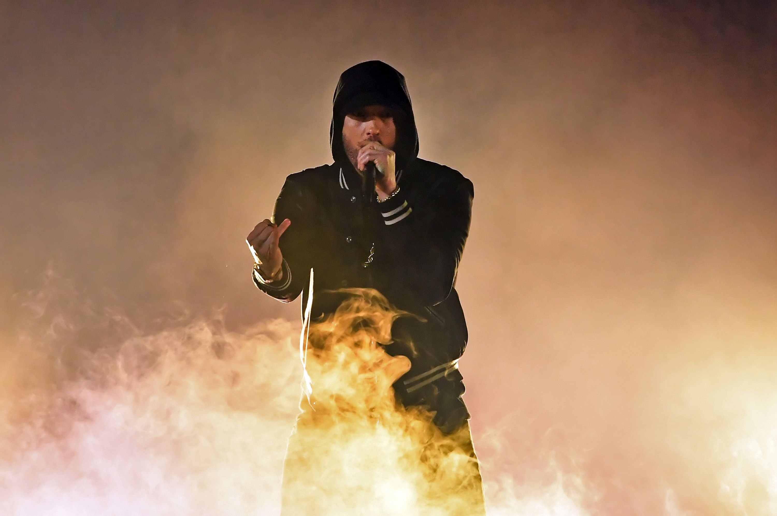 Eminem performing in front of a fire.