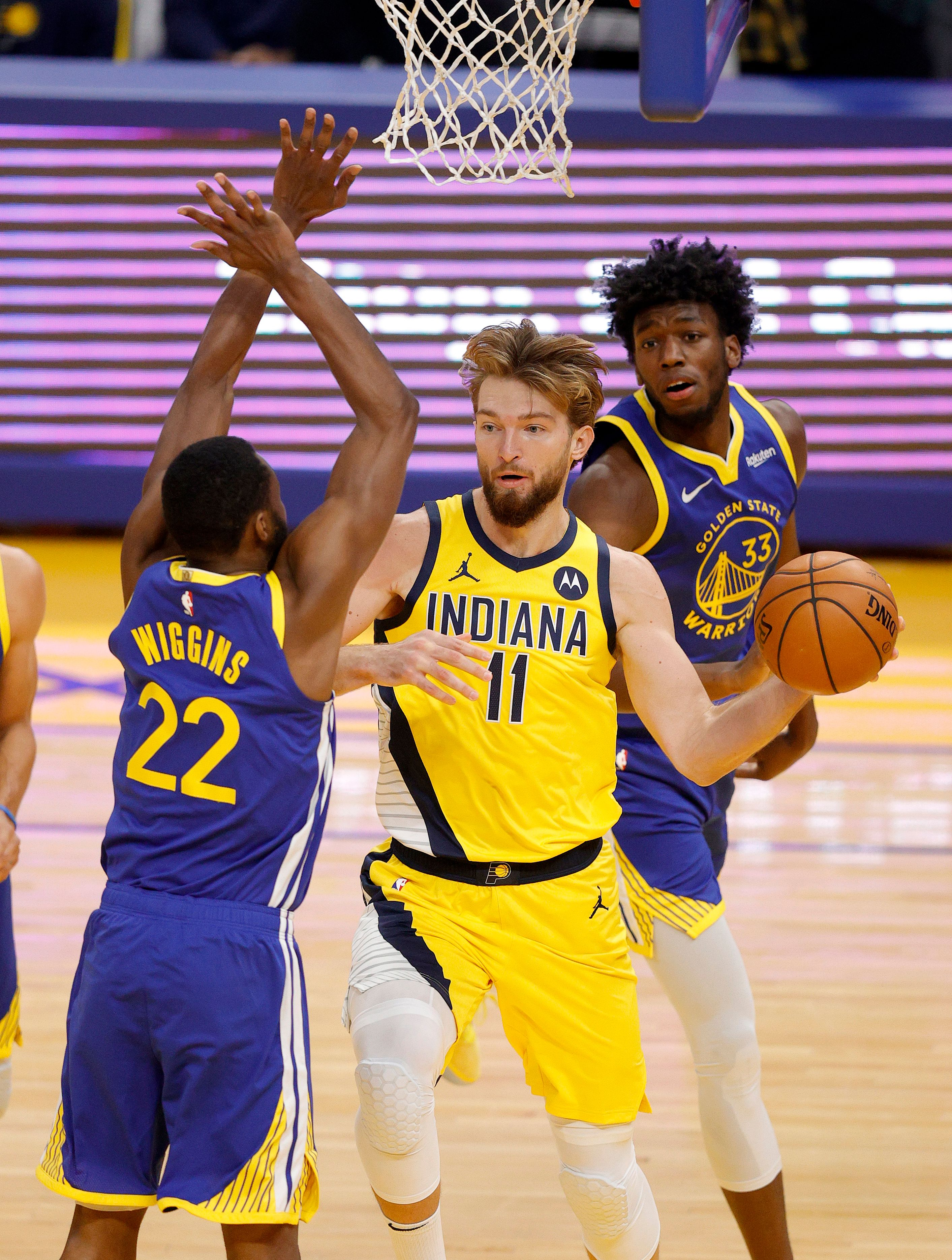 James Wiseman and Andrew Wiggins trying to steal the ball from Domantas Sabonis
