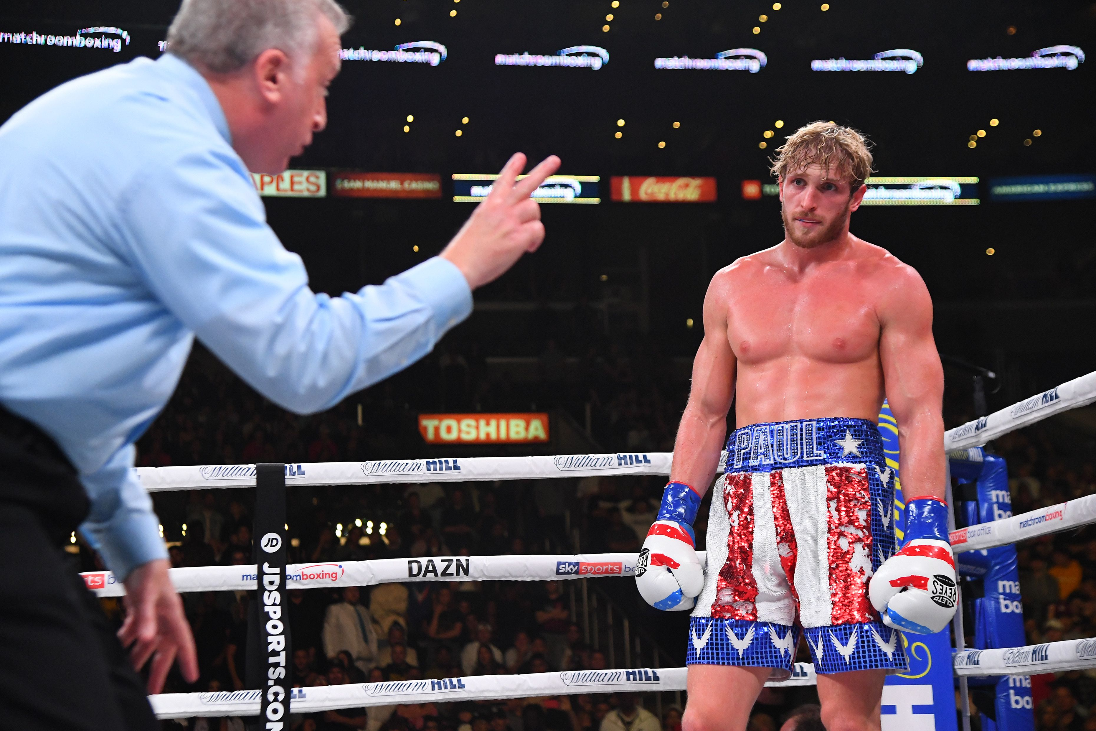 Logan Paul looks at the referee during his boxing match.