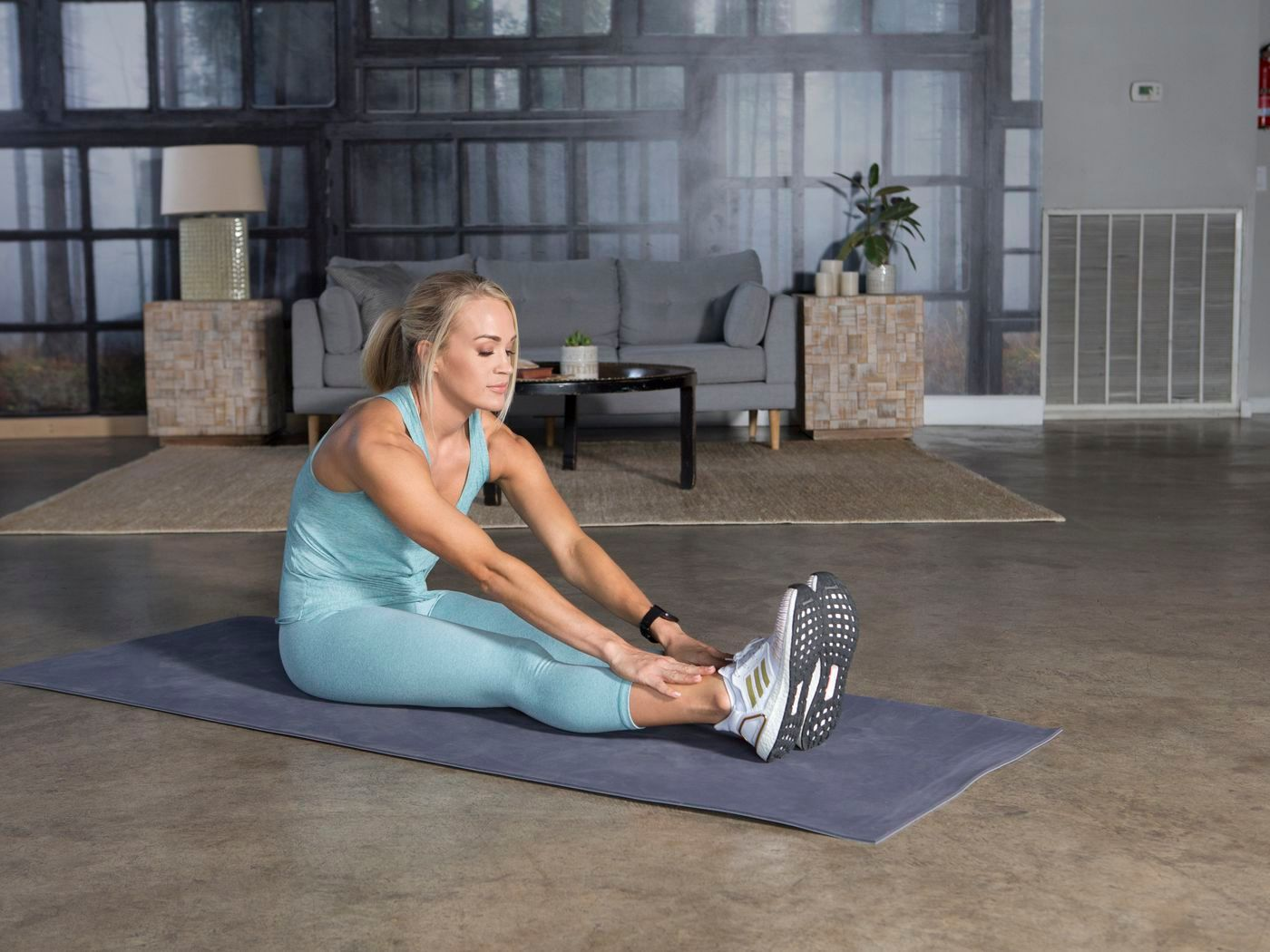Carrie Underwood stretching on the floor