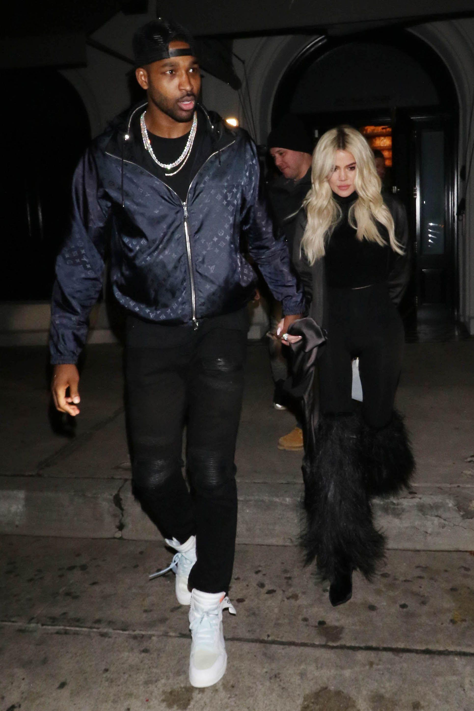 Tristan Thompson (left) walks holding hands with Khloé Kardashian (right)
