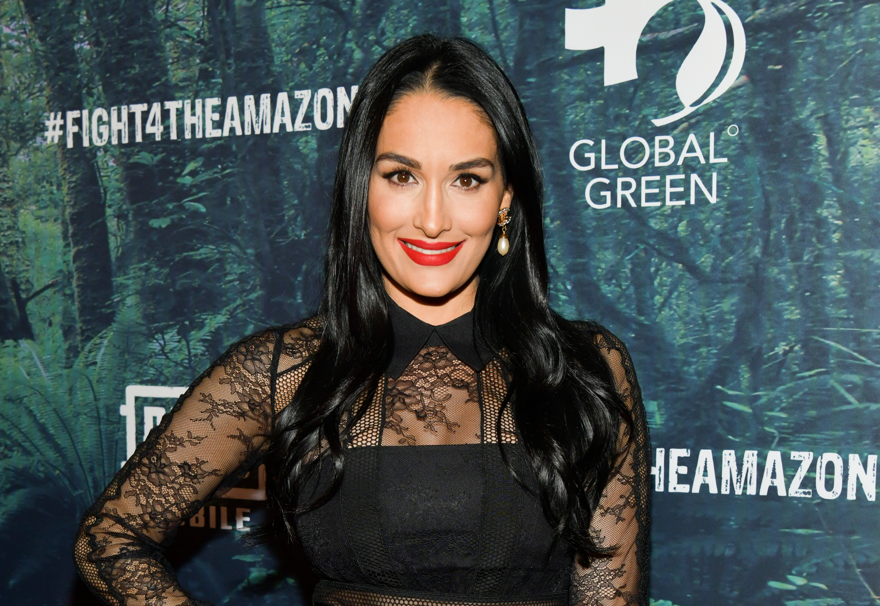 Nikki Bella smiles and poses at a charity event.