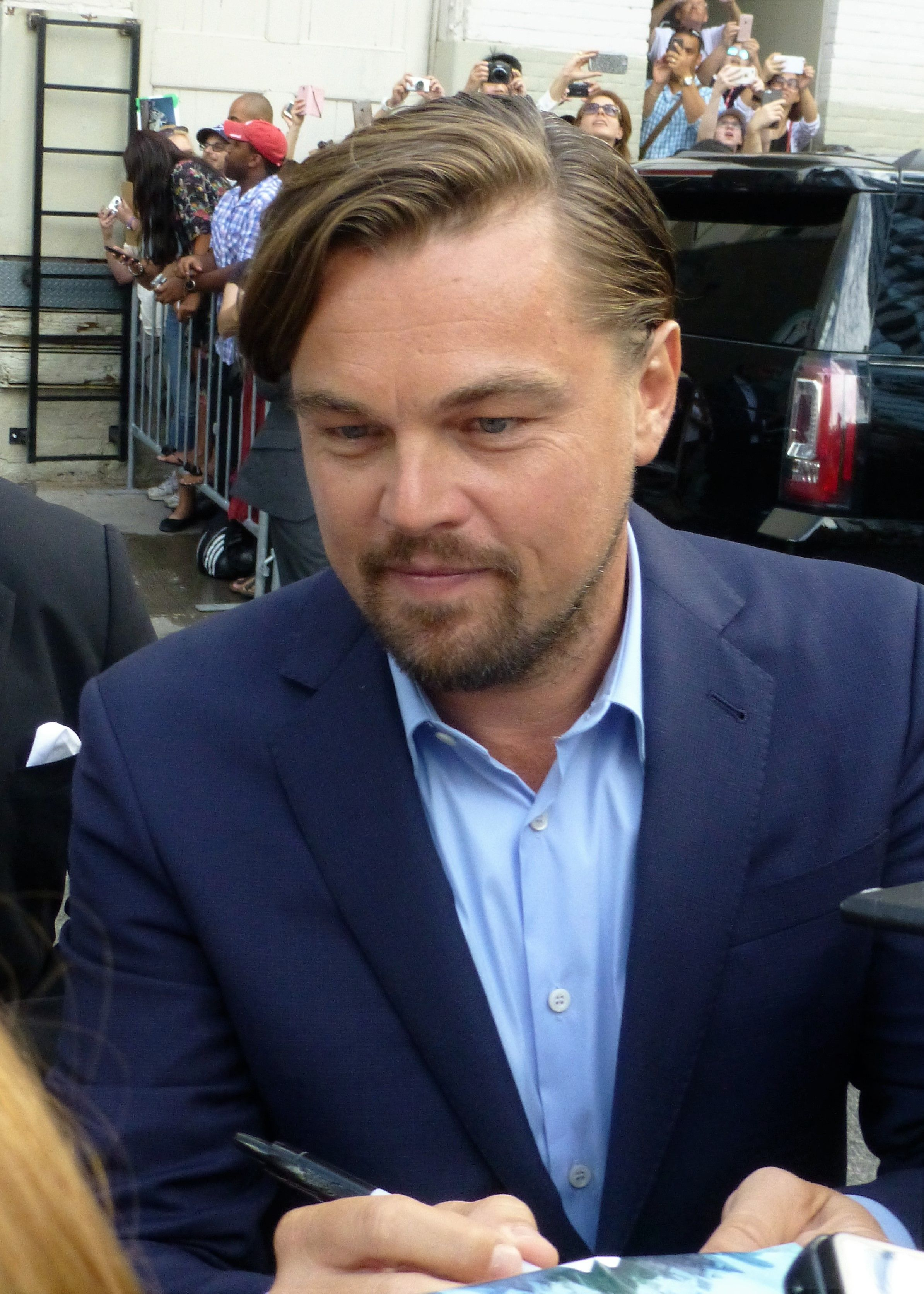 A photo showing Leonardo DiCaprio giving out autographs to his lovely fans at an event.